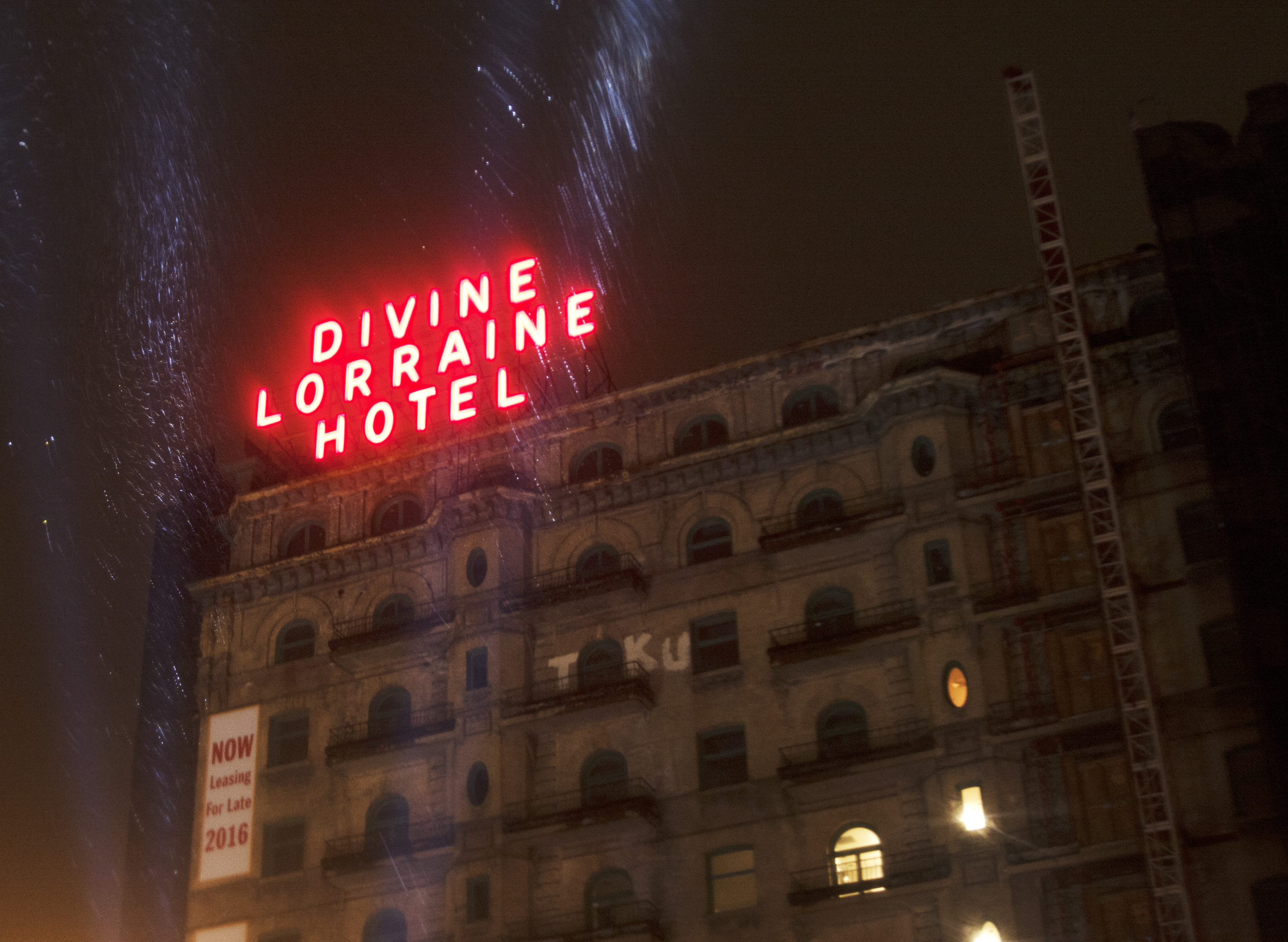The Divine Lorraine Hotel with its iconic neon-red sign lit up.
