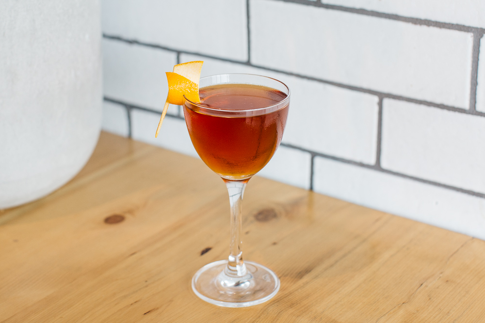A brown cocktail with orange peel garnish in a coup on a wood counter with a white subway tile background at Selden Standard.