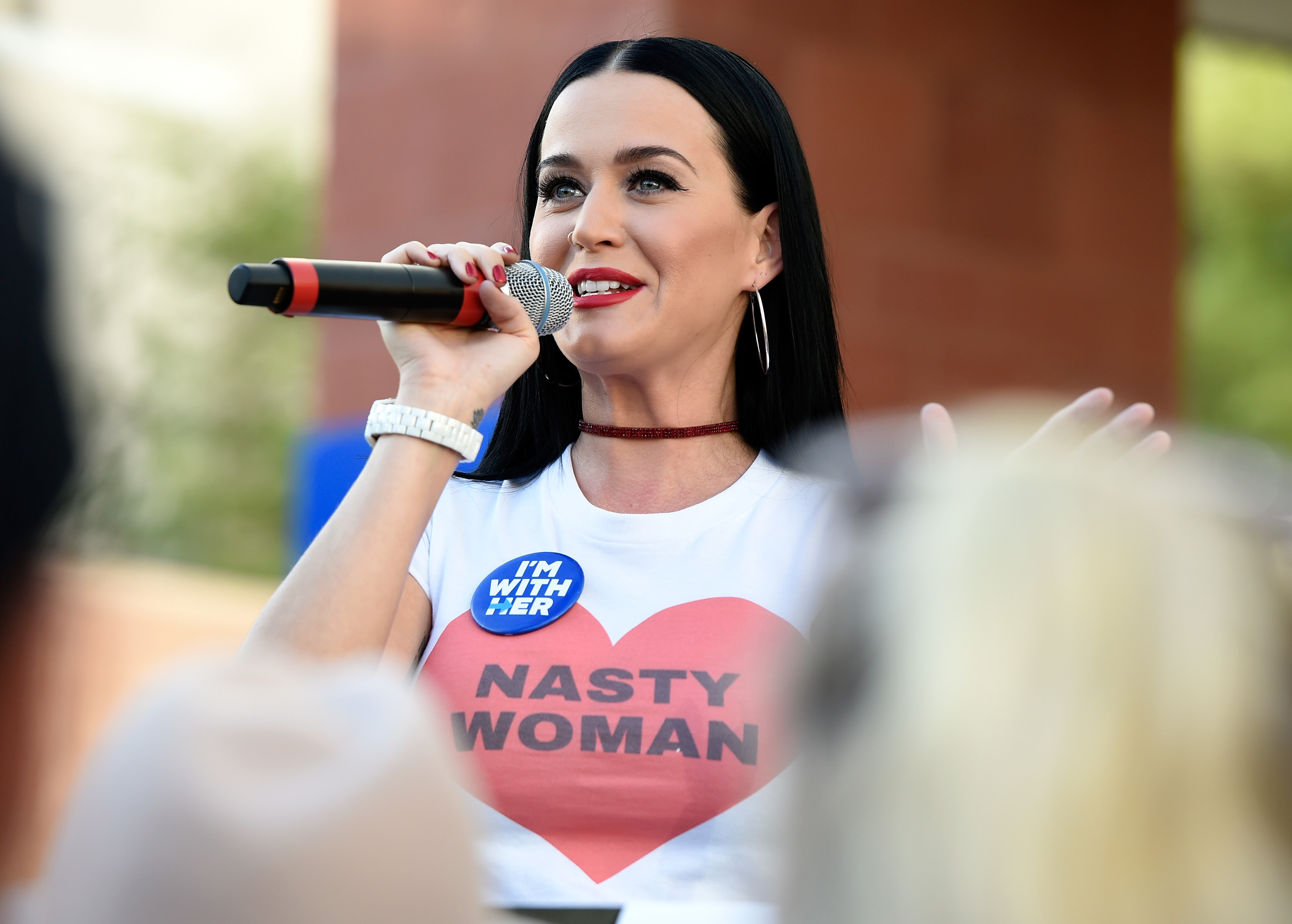 """Katy Perry wearing a """"Nasty Woman"""" shirt while speaking into a mic at a political rally"""