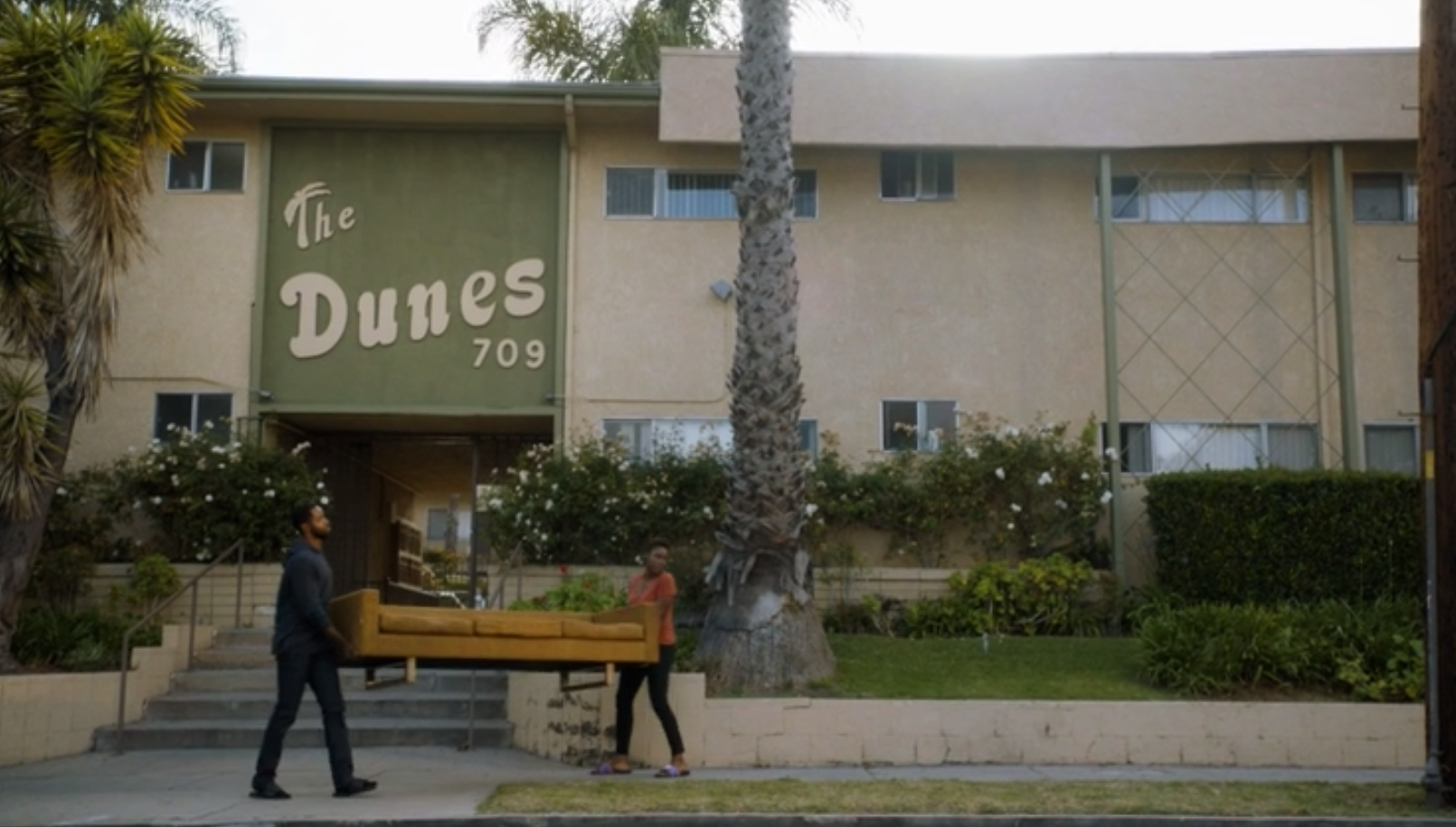 A scene from the HBO show Insecure. Two people carry an orange couch outside of a building in Los Angeles. The sign on the building reads The Dunes 709.