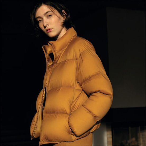 Uniqlo U look book photo featuring model wearing beige puffer coat.