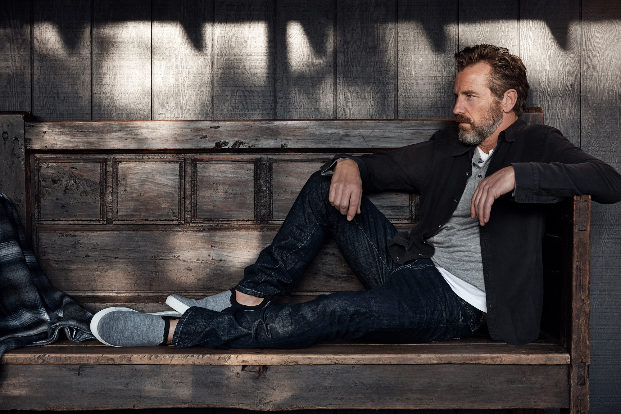 A male model sitting on a bench in James Perse clothes