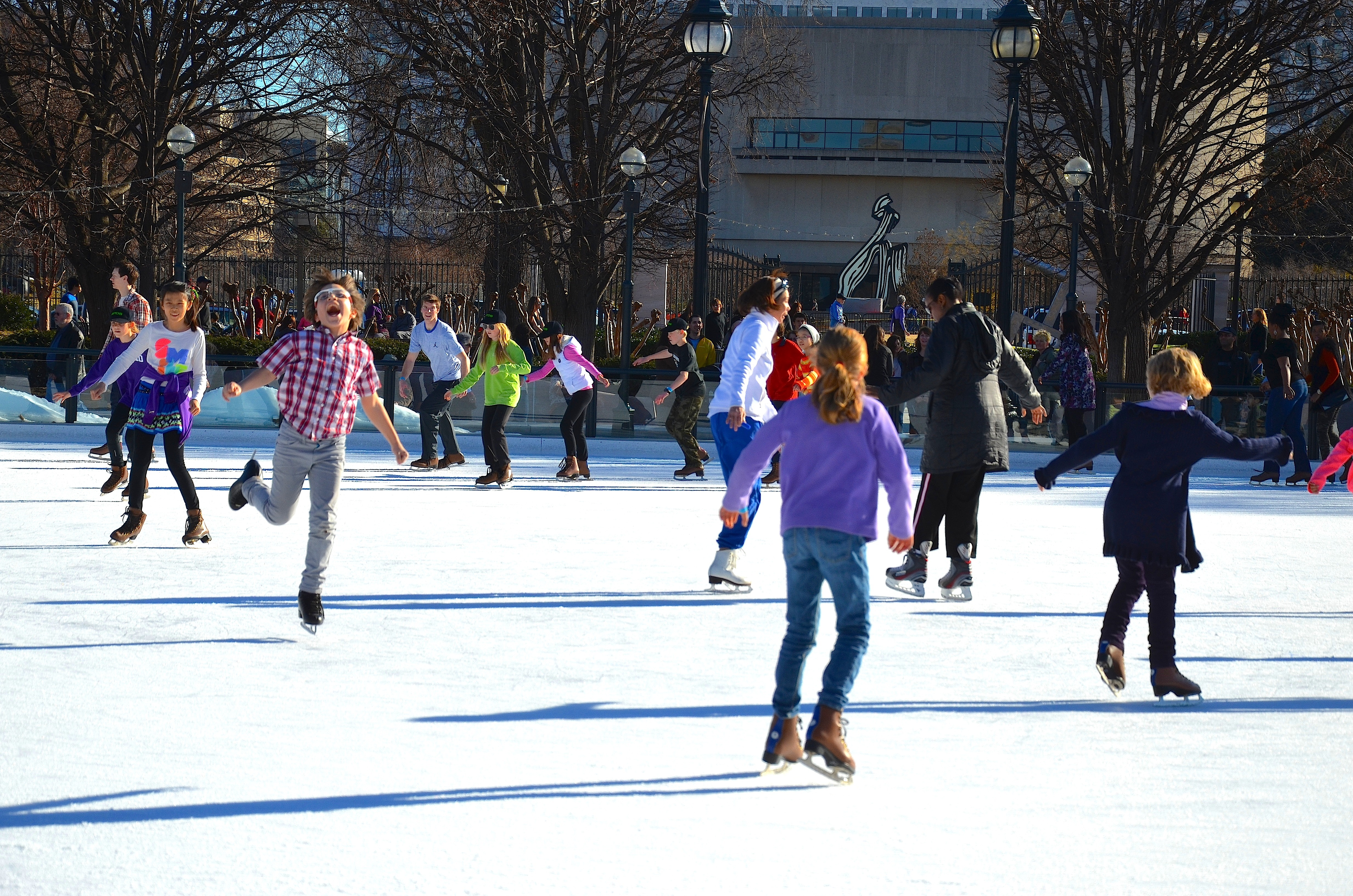A group of kids go ice-skating at an outdoor rink.