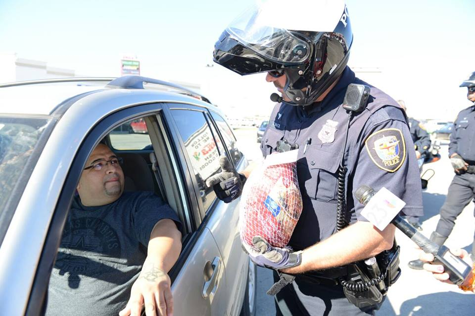 A police officer hands a turkey to a pulled-over motorist.