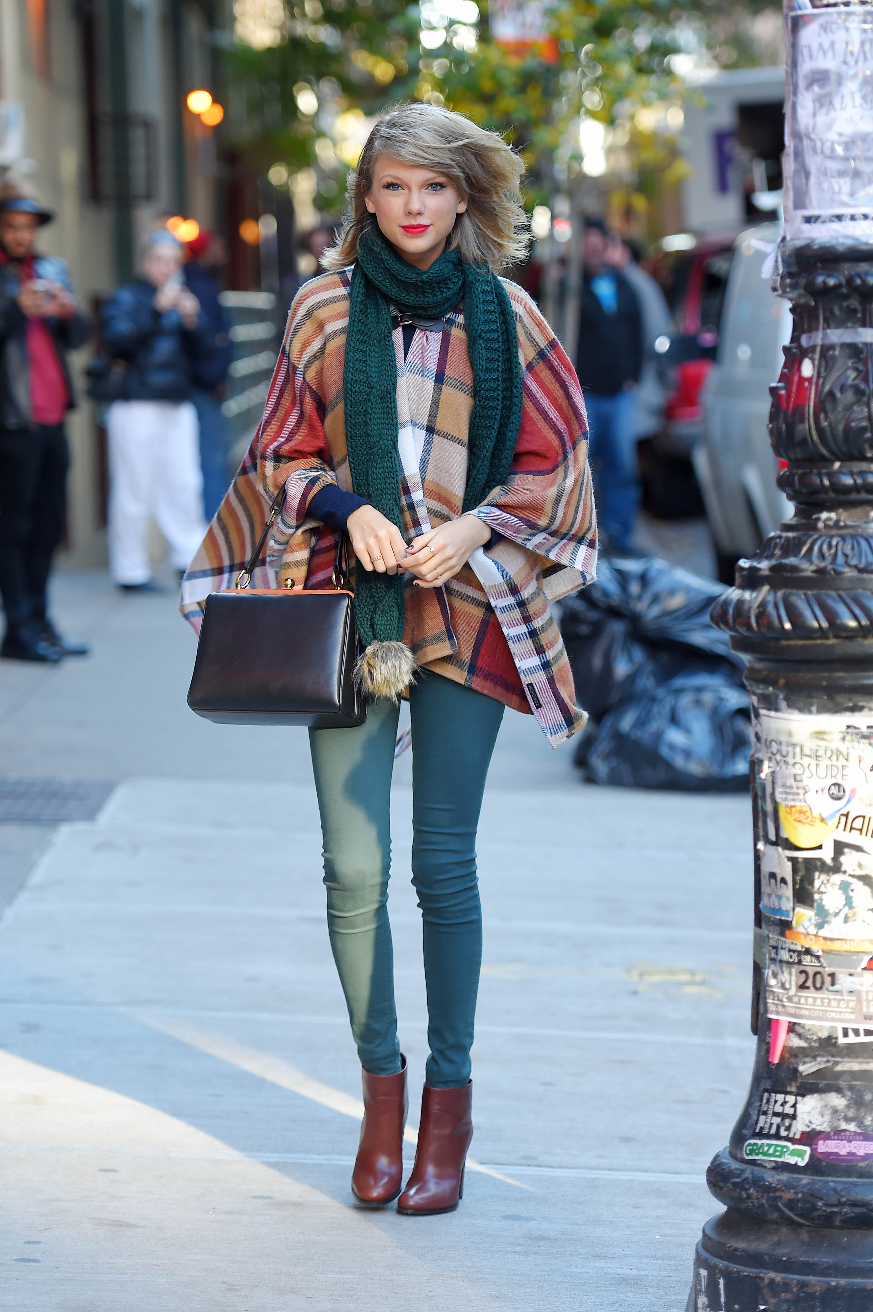 Swift wears a Topshop cape and scarf, Hudson jeans, Prada boots, and Dolce & Gabbana bag on November 14th, 2014.