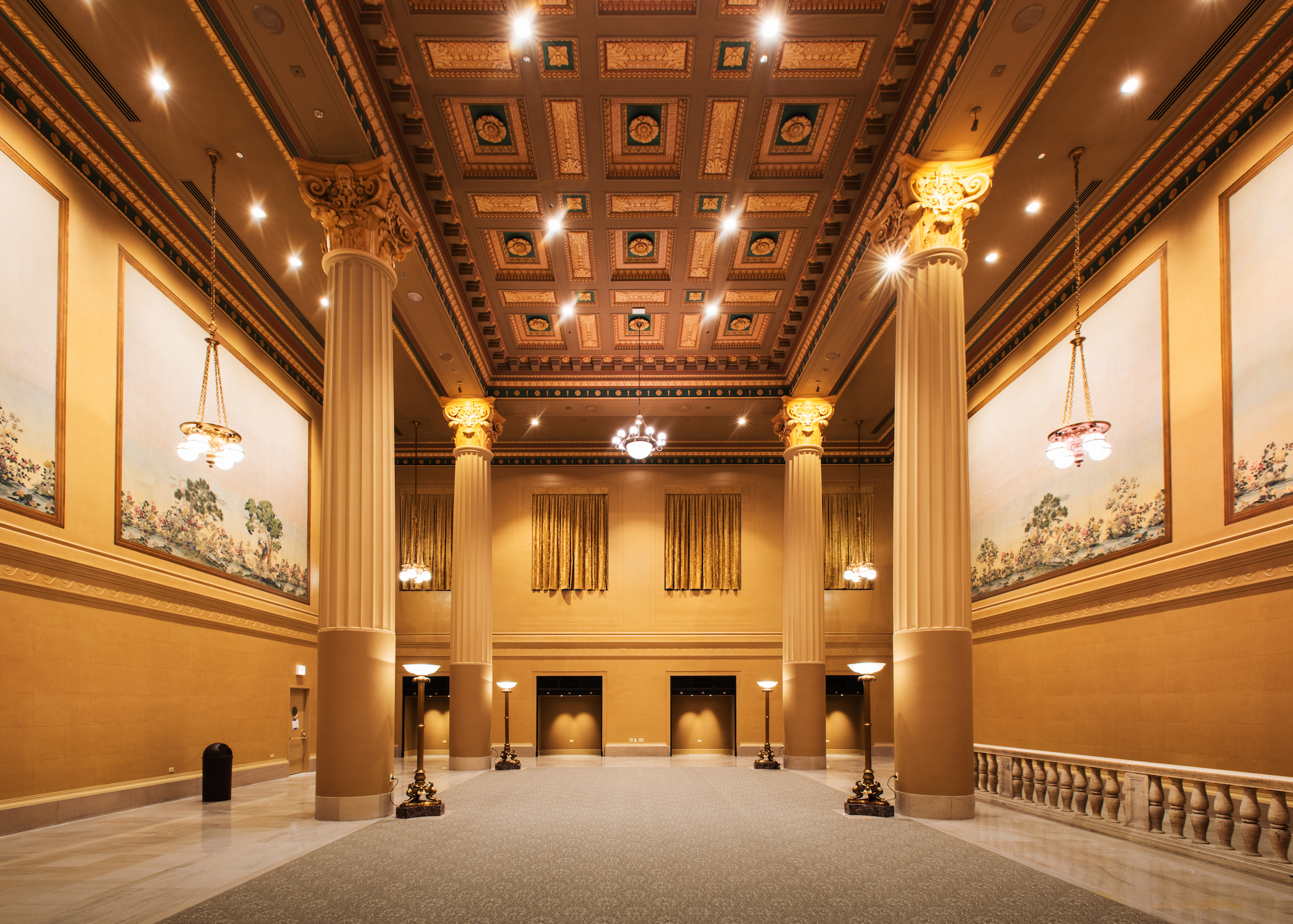 The interior of an event venue. The walls are yellow and the ceiling is wooden with a carved design. There are columns.