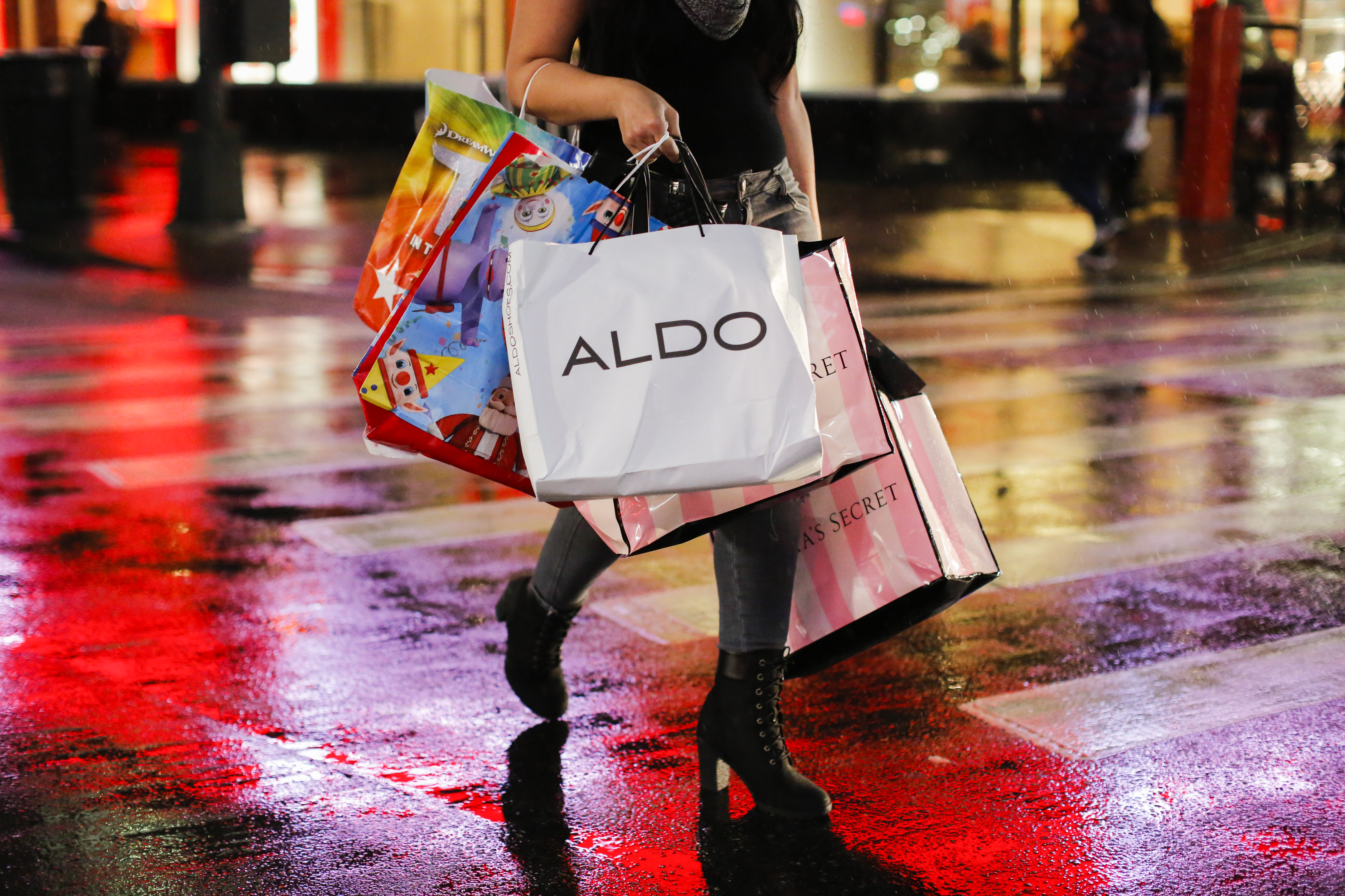 A woman crosses the street toting five shopping bags.