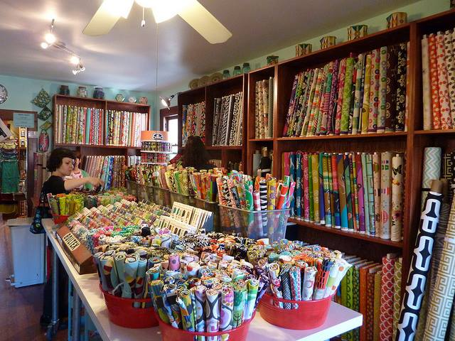 A room full of colorful fabrics and notions with a woman shopping at the end of the room