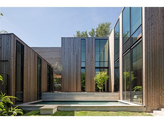 two-story contemporary with blocky design, two-story windows, and slatted wooden facade