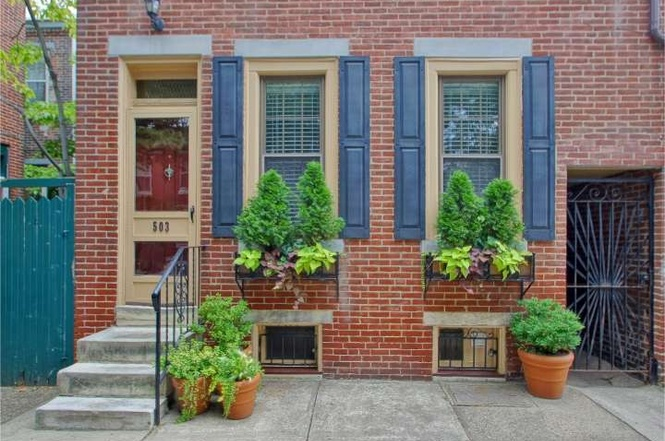 A brick home with blue shutters, flower boxes, and a red door.