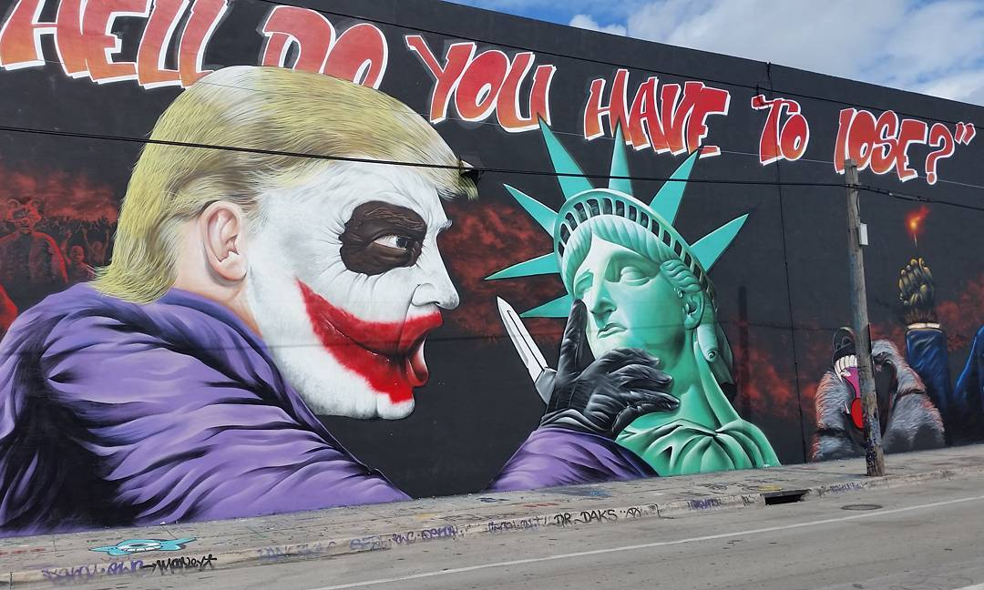 A mural of Donald Trump as the Joker in Wynwood with a purple suit, eyeing the statue of liberty