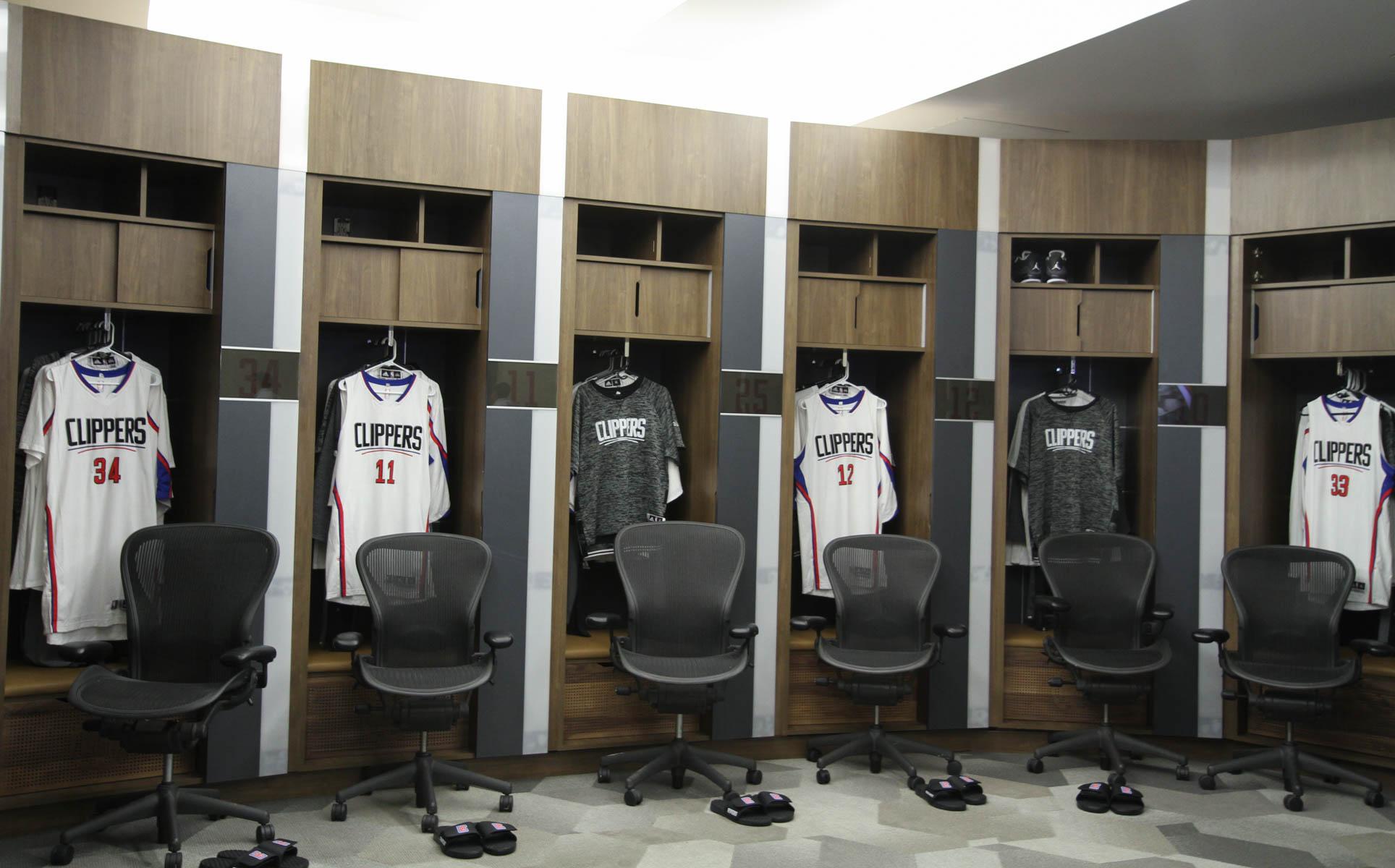 Shot of lockers with chairs and shower slippers in front of each one
