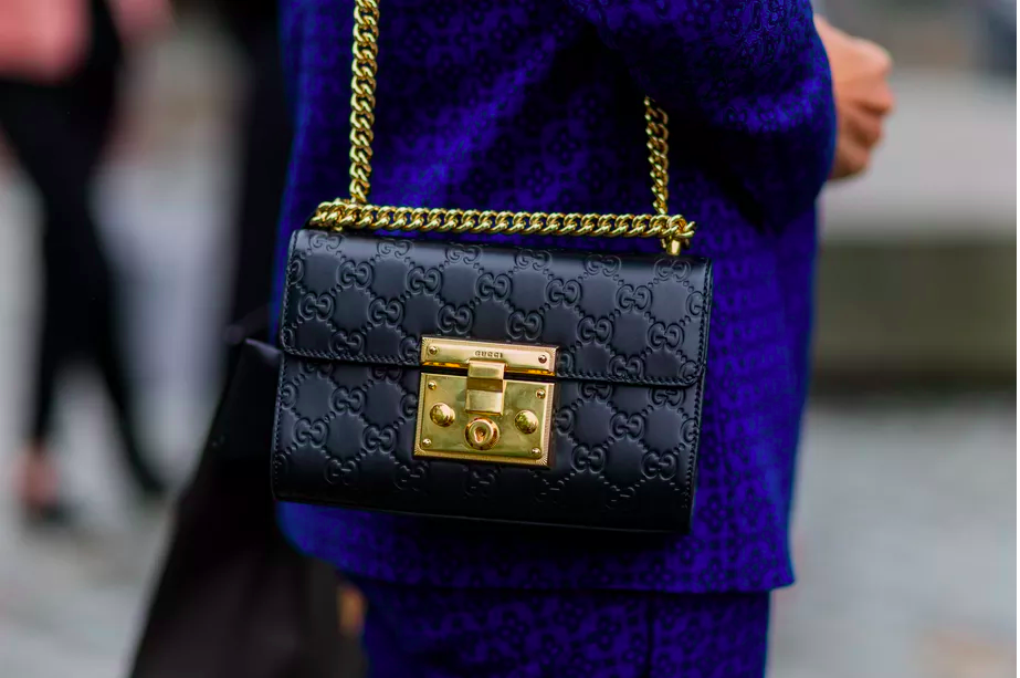 A close-up of a black Gucci shoulder bag with gold detail.