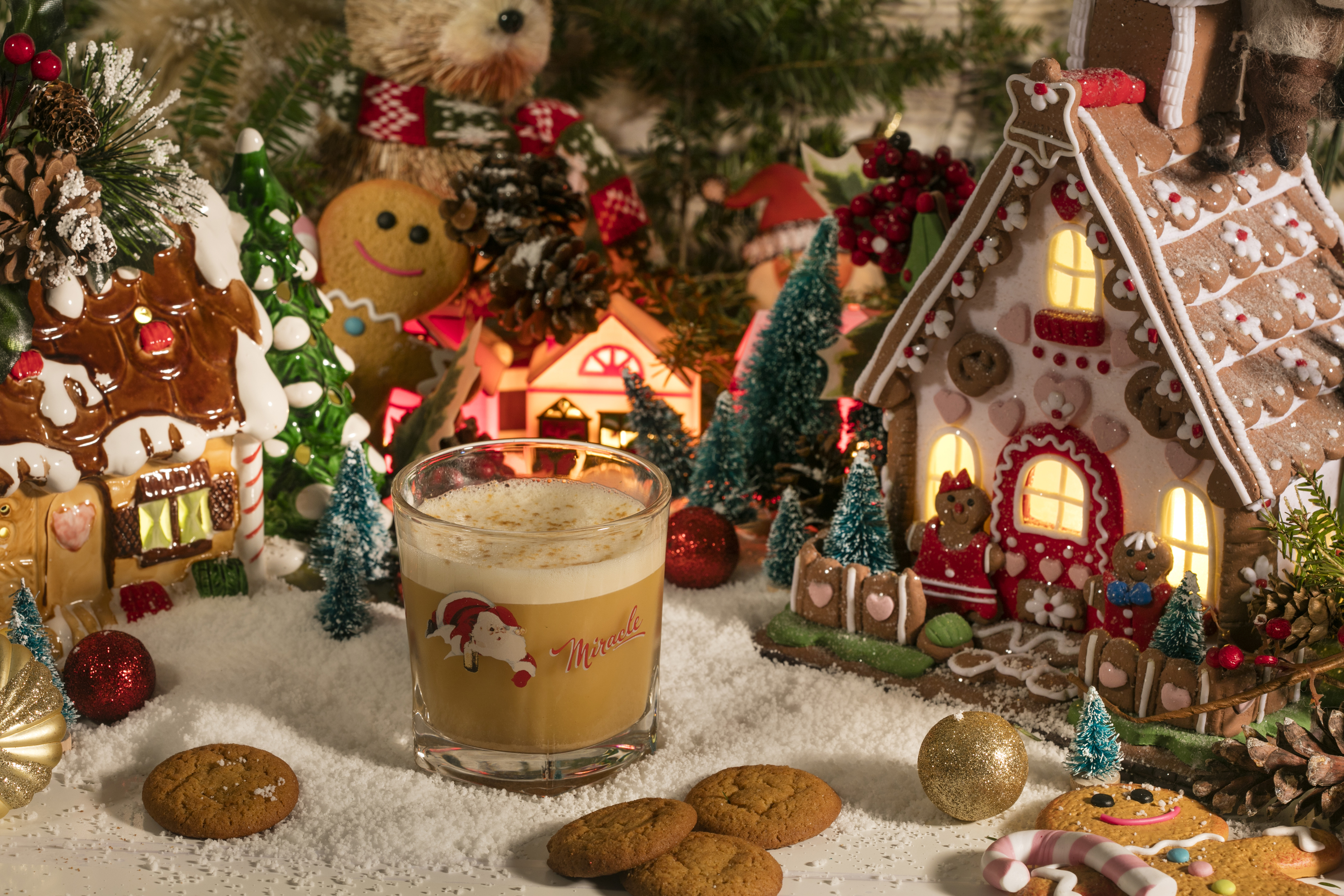 A holiday gingerbread tableau with a glass of eggnog surrounded by fake snow, toys, miniature trees, and cookies.