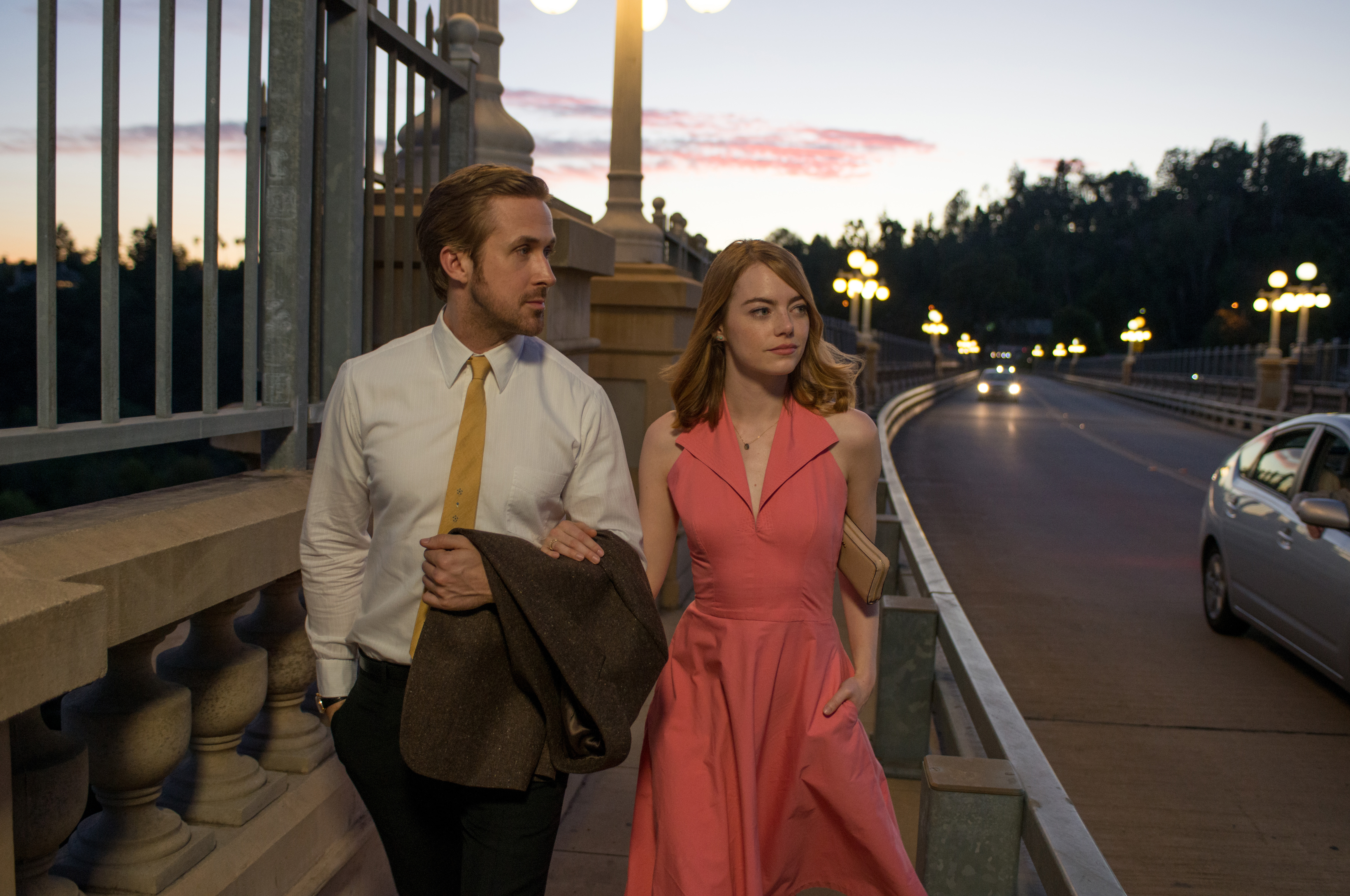 A man and a woman walk down a sidewalk which is adjacent to a street. There are lamp posts with lights on lining the street. The woman is in a red dress. The man is in a suit carrying his jacket on one arm.