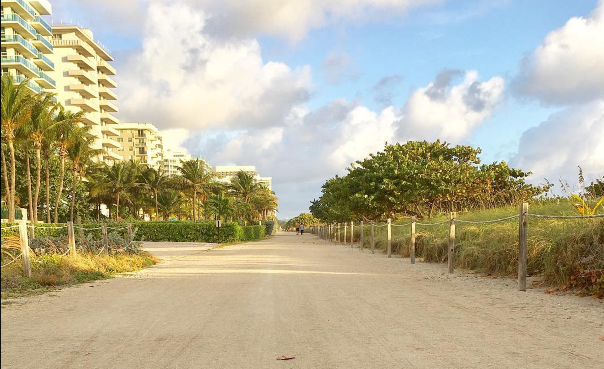 Just beyond the beach with buildings to the left and a lush divider to the right