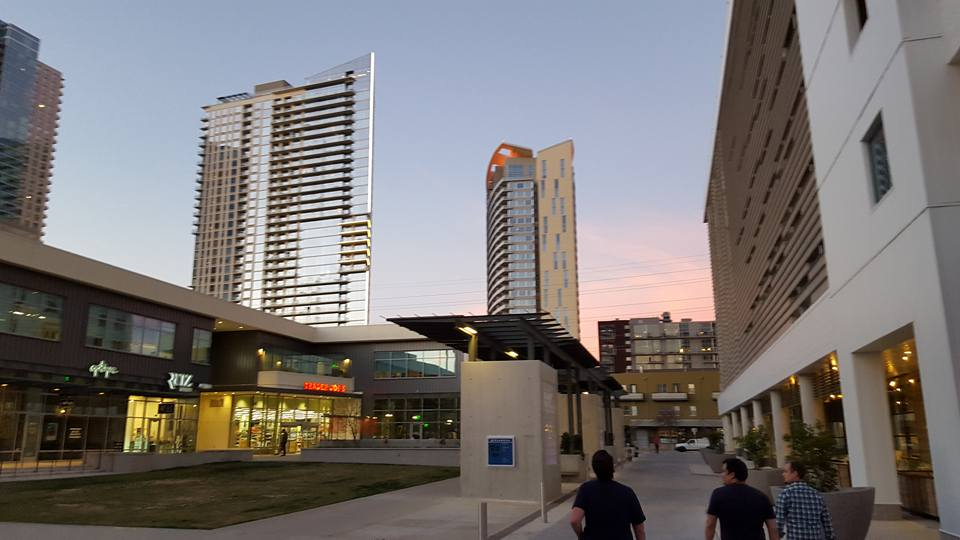 people walking in a sort of outdoor urban mall with grass in the middle and skyscrapers in background
