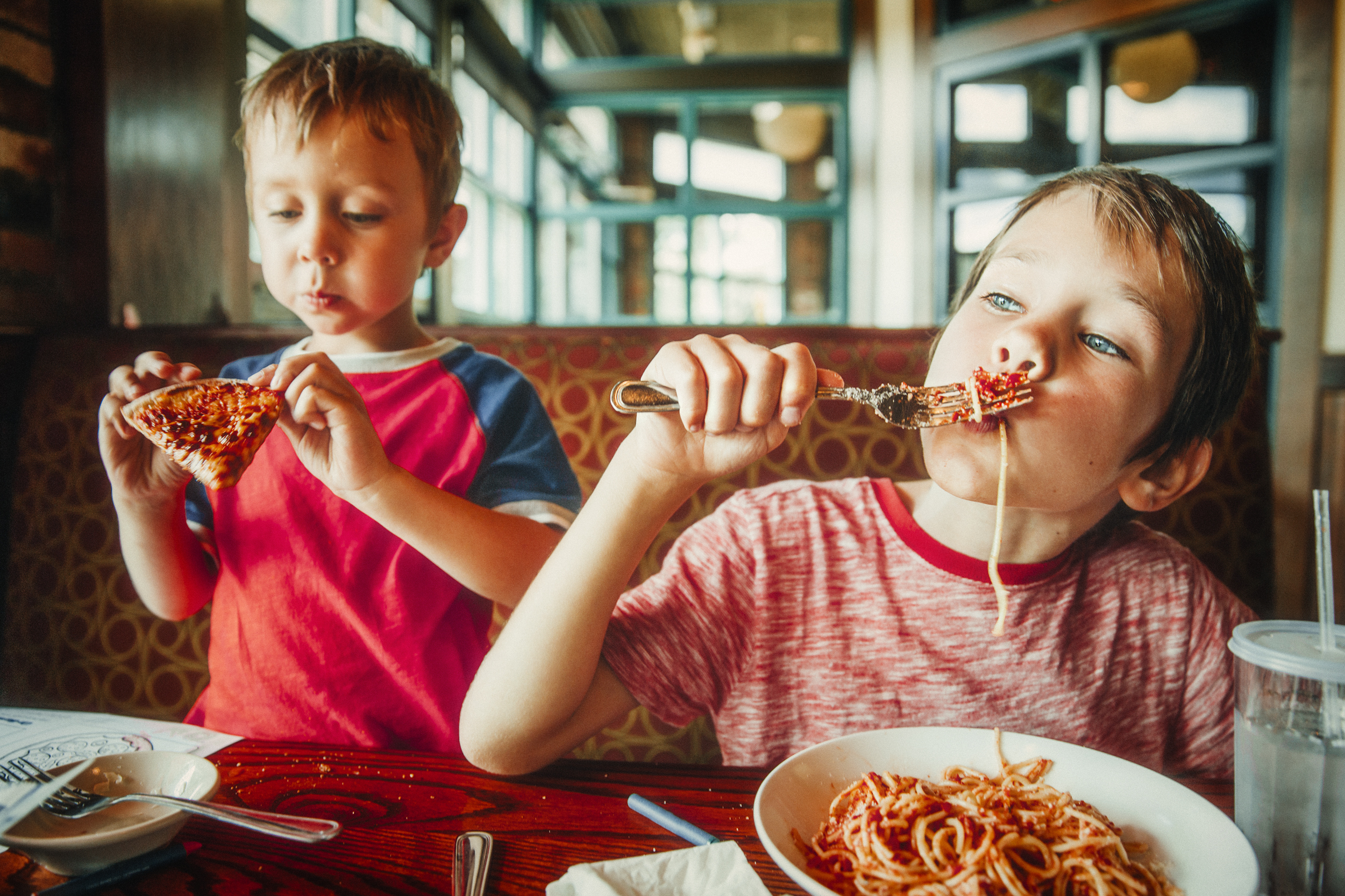 A picture of two kids eating pizza and spaghetti