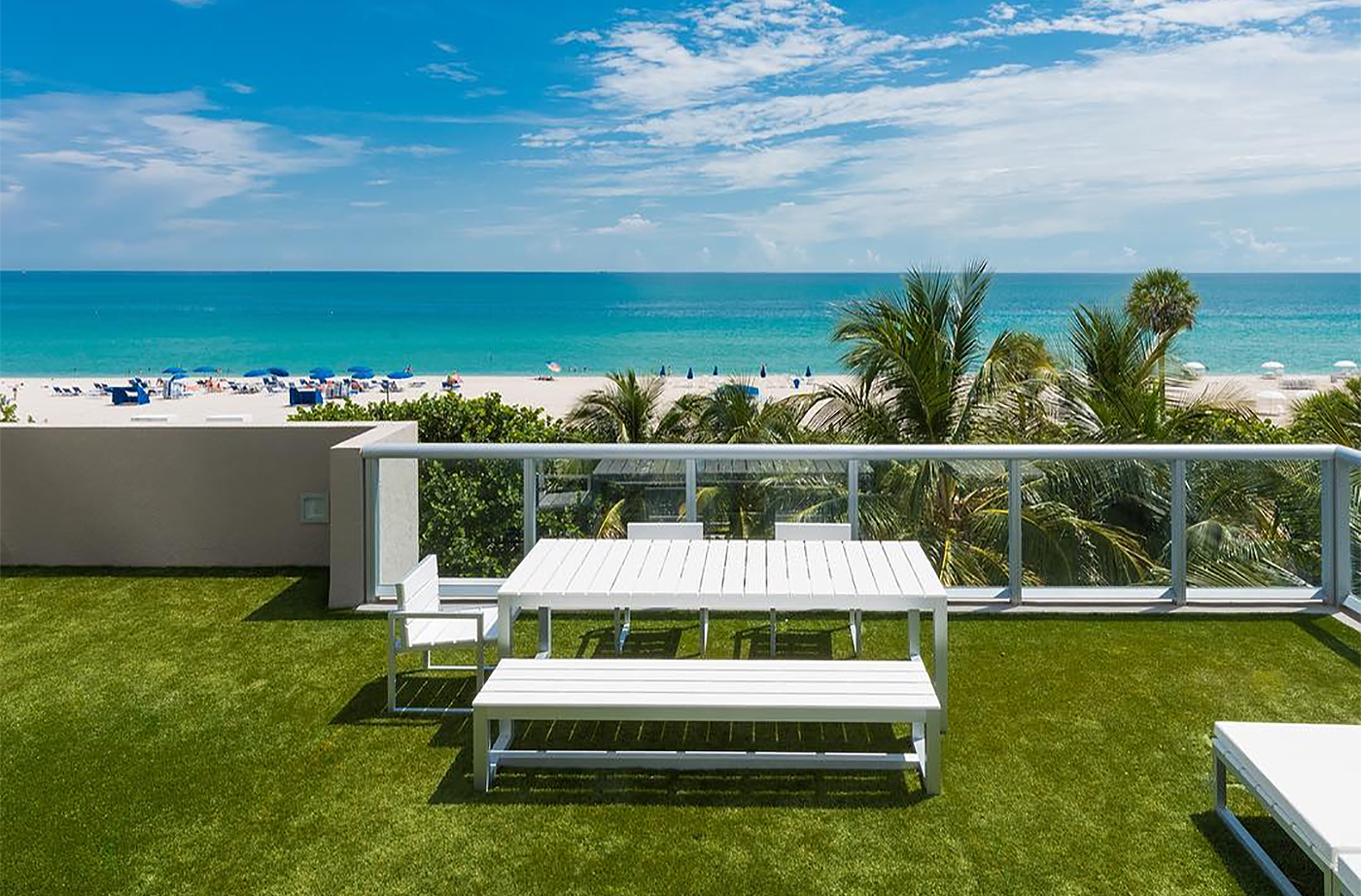 Backyard terrace with turf, white table, and the ocean and beach in the background