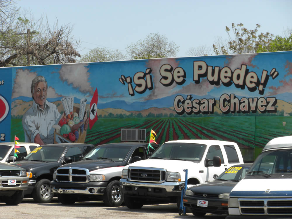 """A mural of Cesar Chavez that says """"Si Se Puede"""" with a car lot in front"""