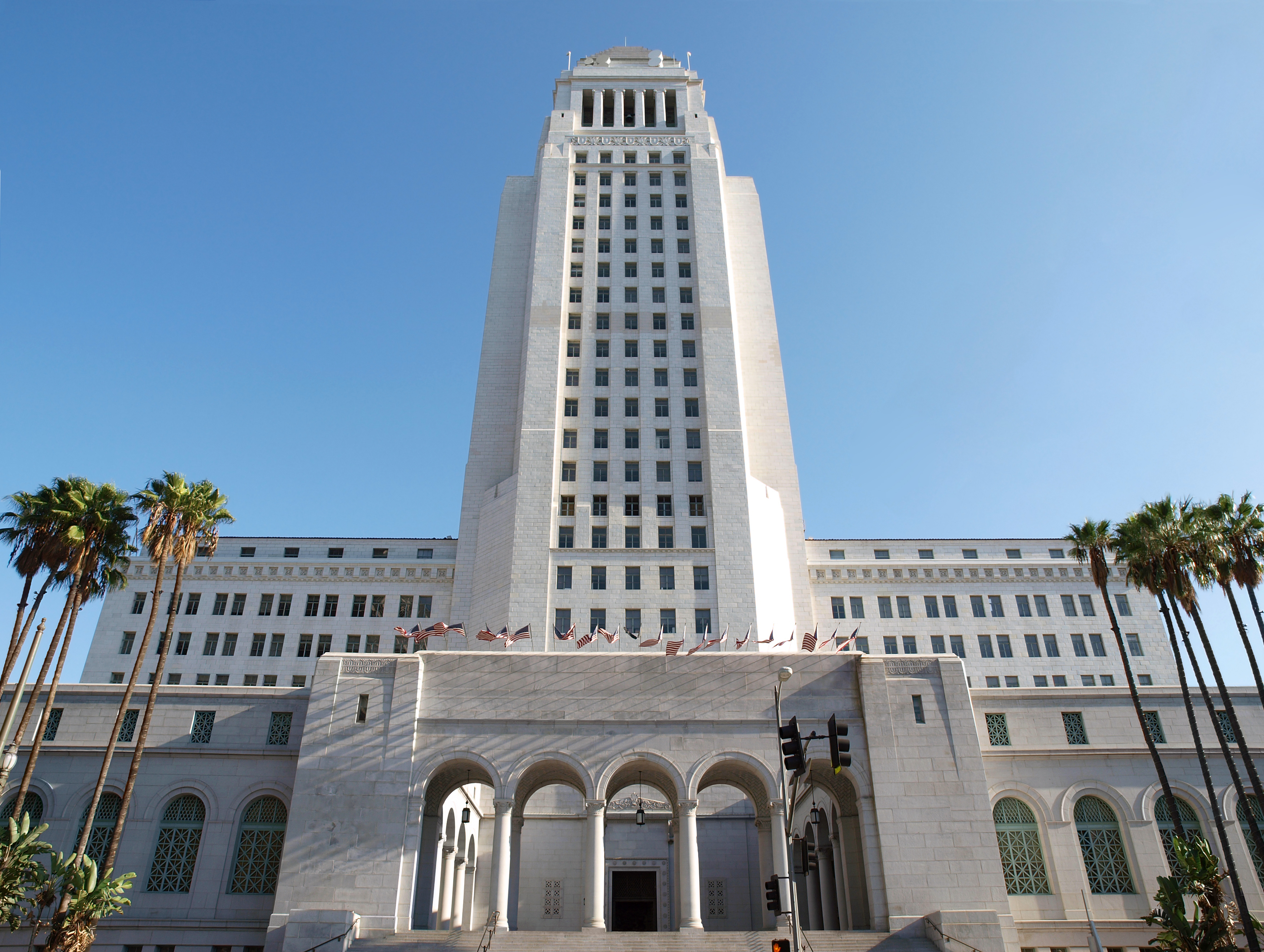 A white building with a tall tower. The front of the building has an arched entryway.