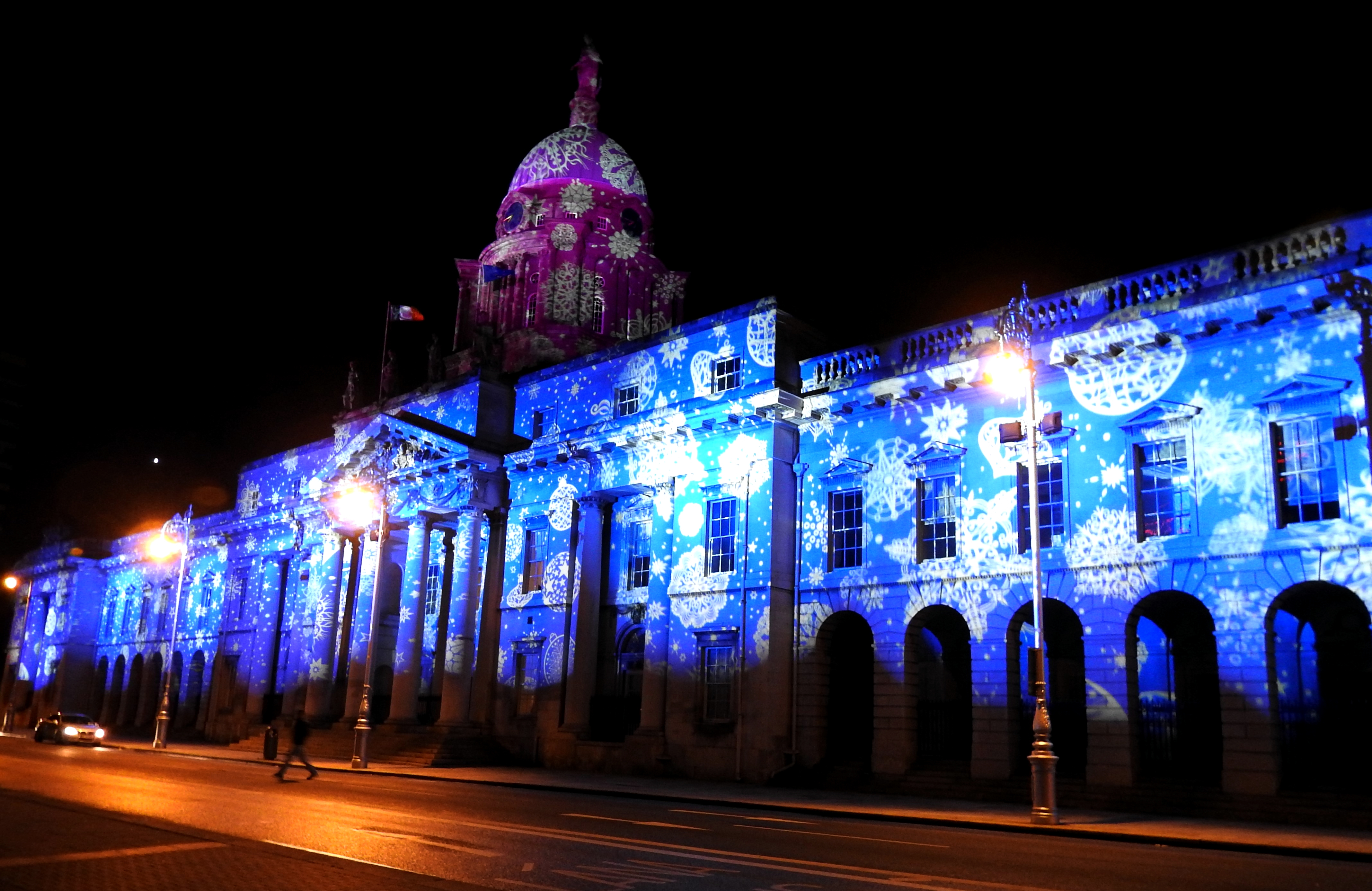 Bright blue and purple snowflakes are projected on an ornate 18th century building at night as part of a Christmas decoration lights display.