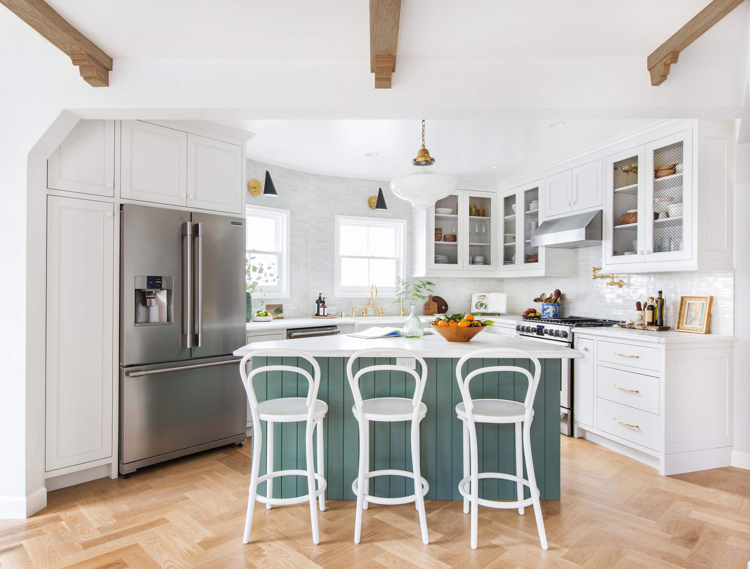 Emily Henderson renovated kitchen, with an island, bar stools, stainless steel appliances and brass hardware.