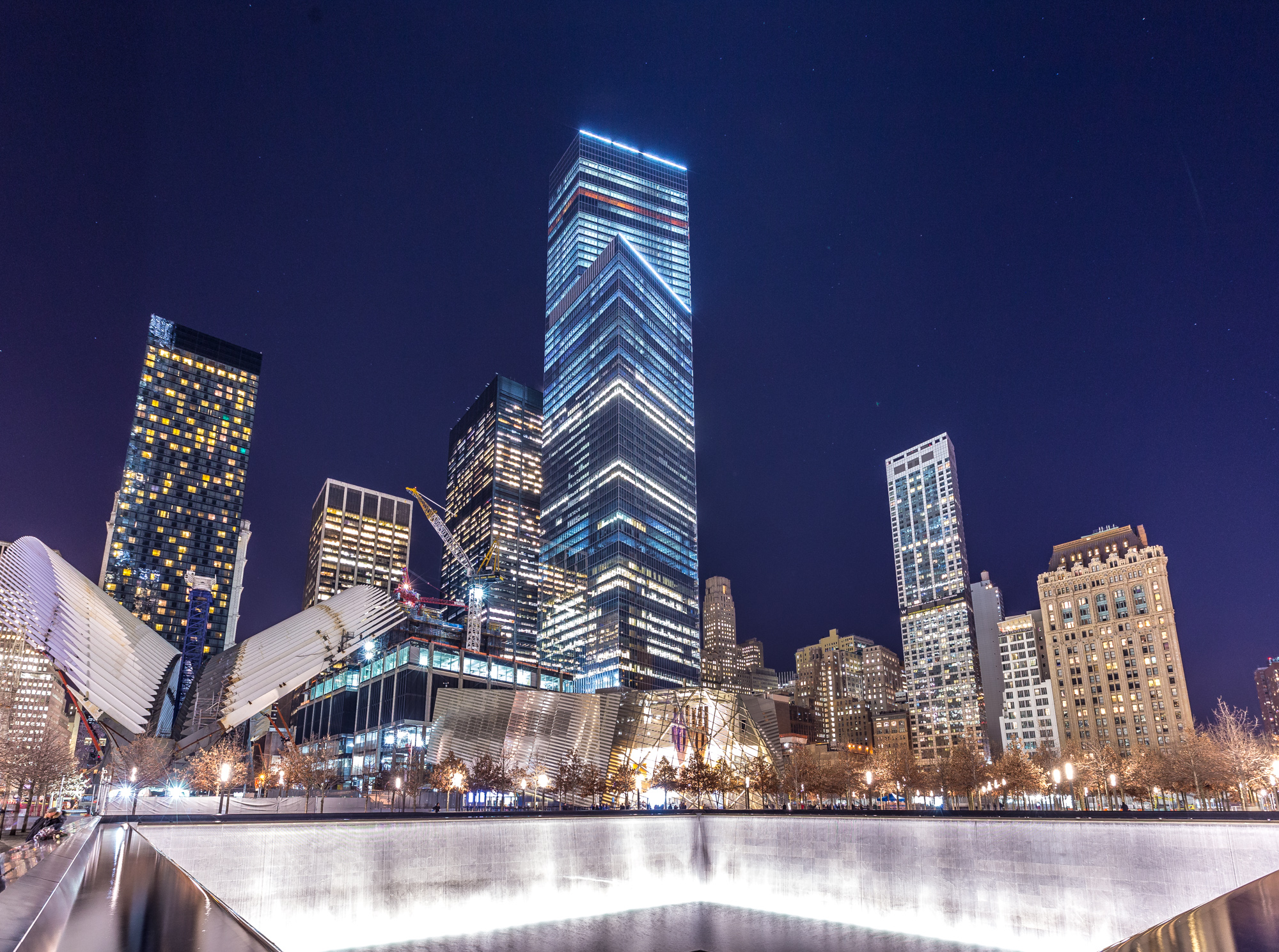 The skyscrapers and buildings at the World Trade Center site. In the foreground is a large memorial fountain.