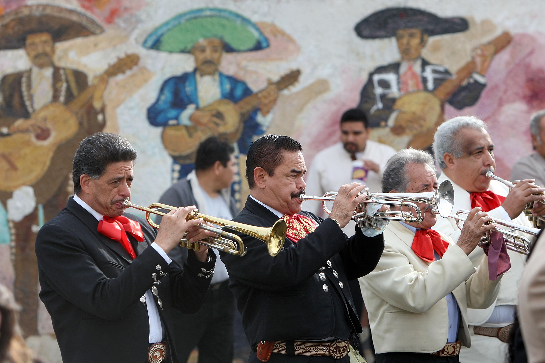 Mariachis play near a mural at Mariachi Plazain Boyle Heights.