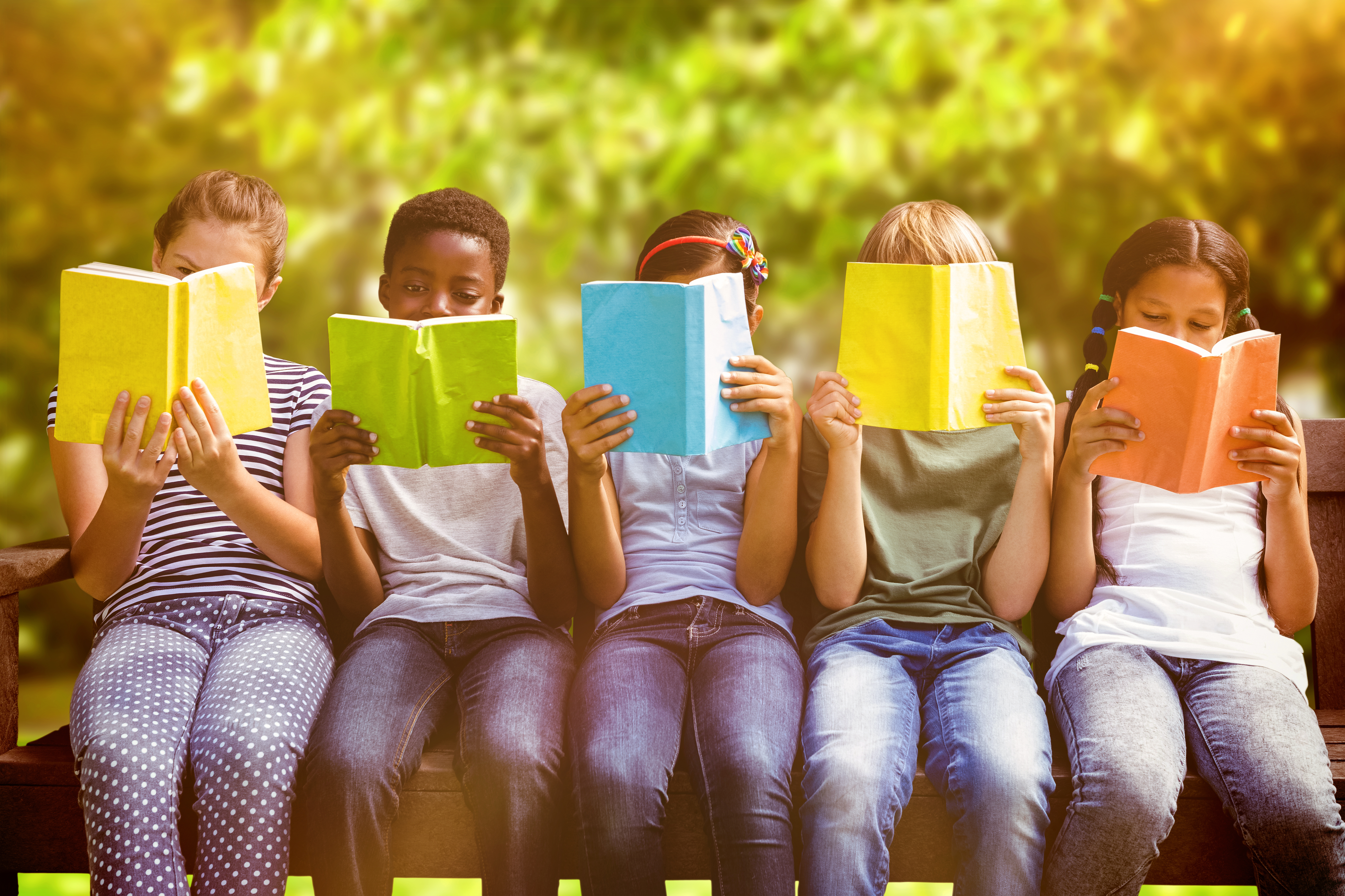children sitting in a row reading books