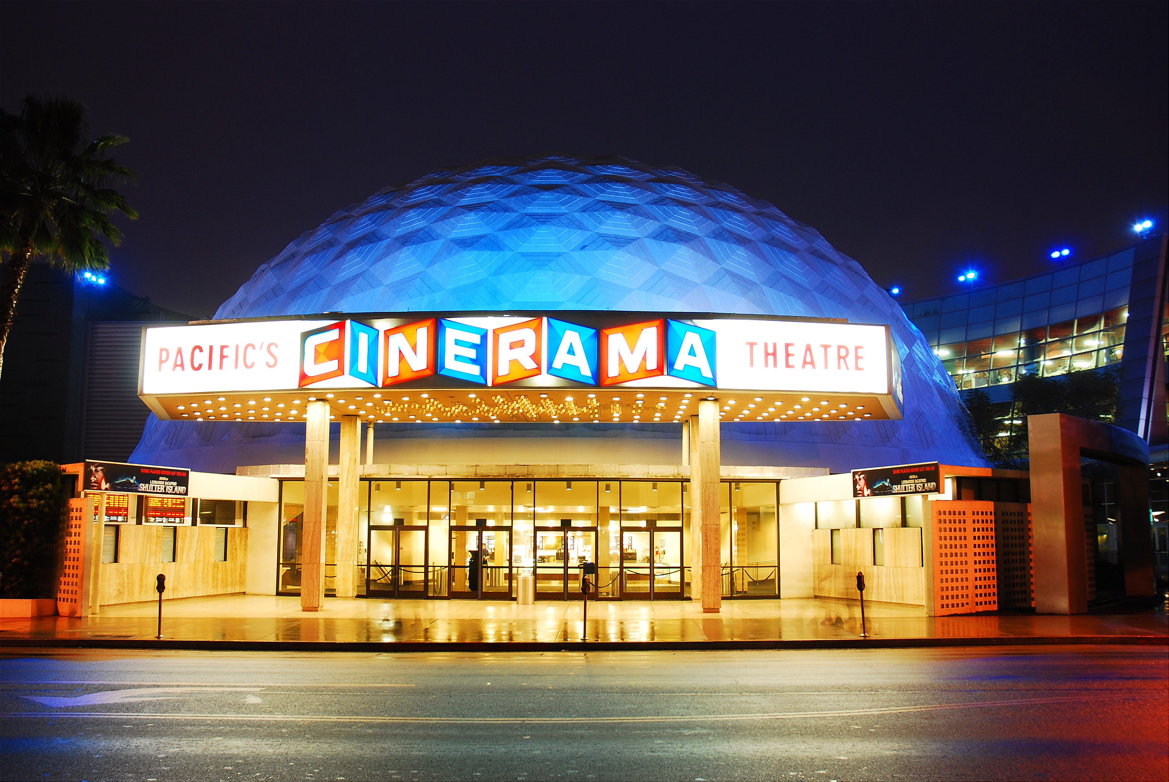 The bright lights of a theater marquee and lobby seen at night, with the outline of a white dome visible in the background