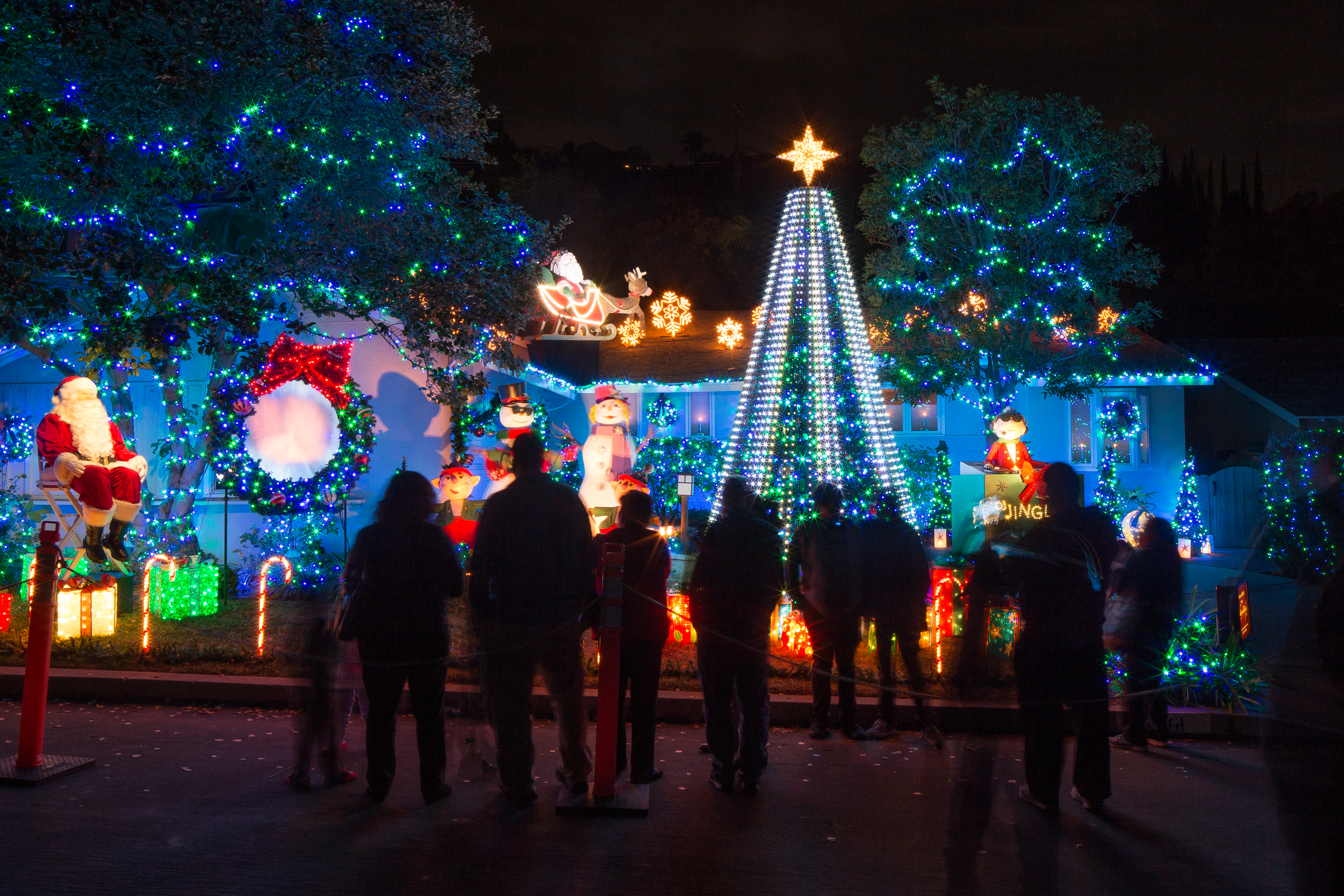 A crowd gathers in front of a glowing holiday display