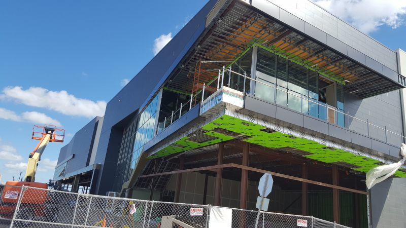 Corner of a two-story commercial building with part metal/part glass walls, balcony, under construction