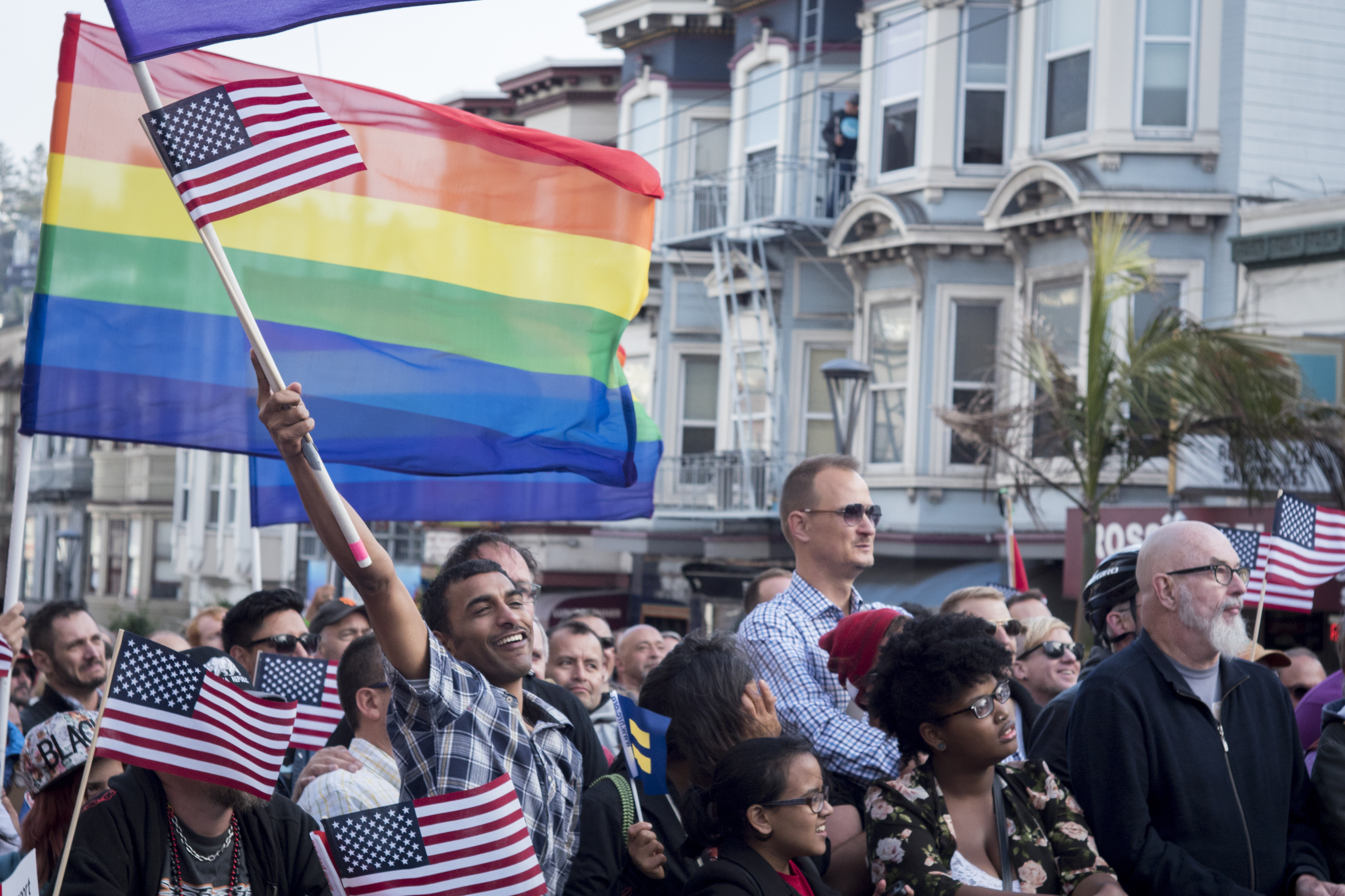 Men and women at a protest with rainbow flags on Castro Street