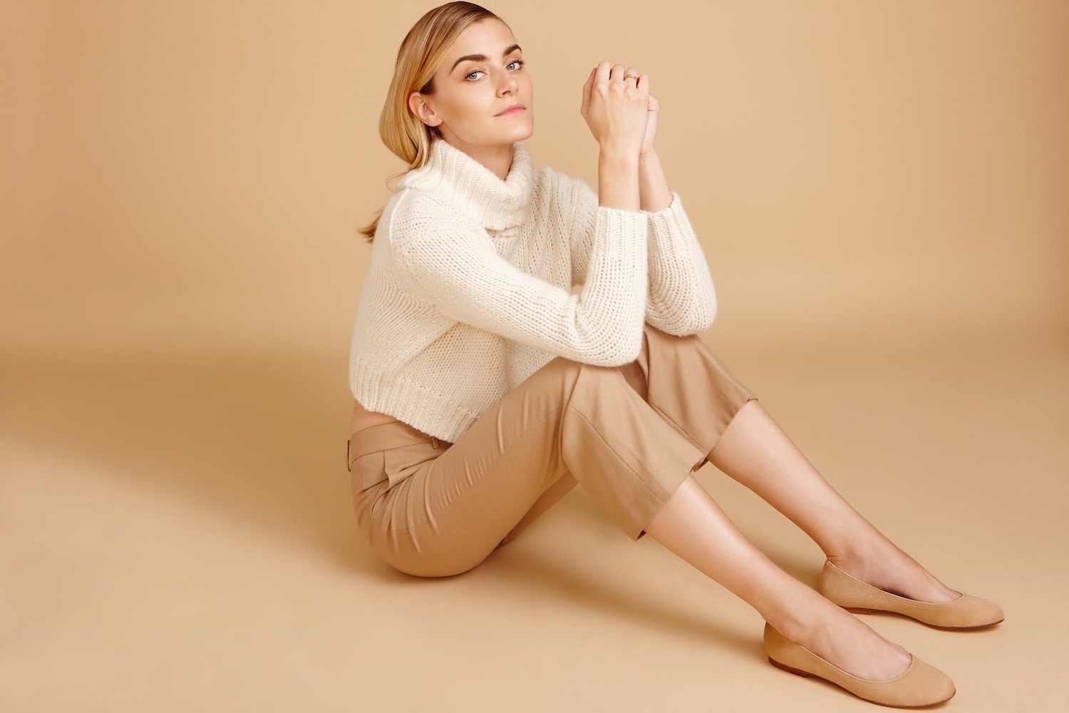 A model wearing camel colored pants and shoes and a white sweater