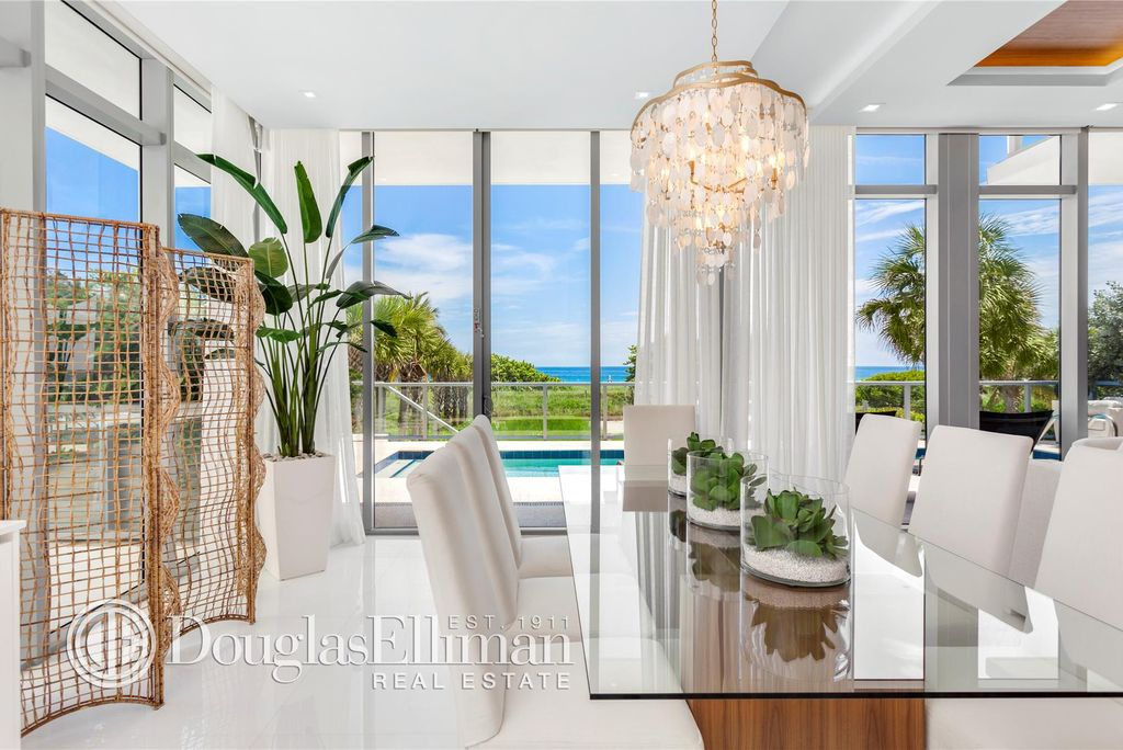 Inside the dining area of a oceanfront townhome in Surfside with  white walls and floors, and a glass table