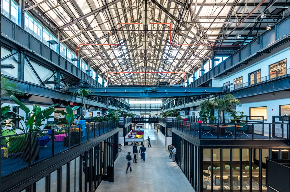 Interior of a former shipbuilding warehouse with soaring roof and industrial beams.