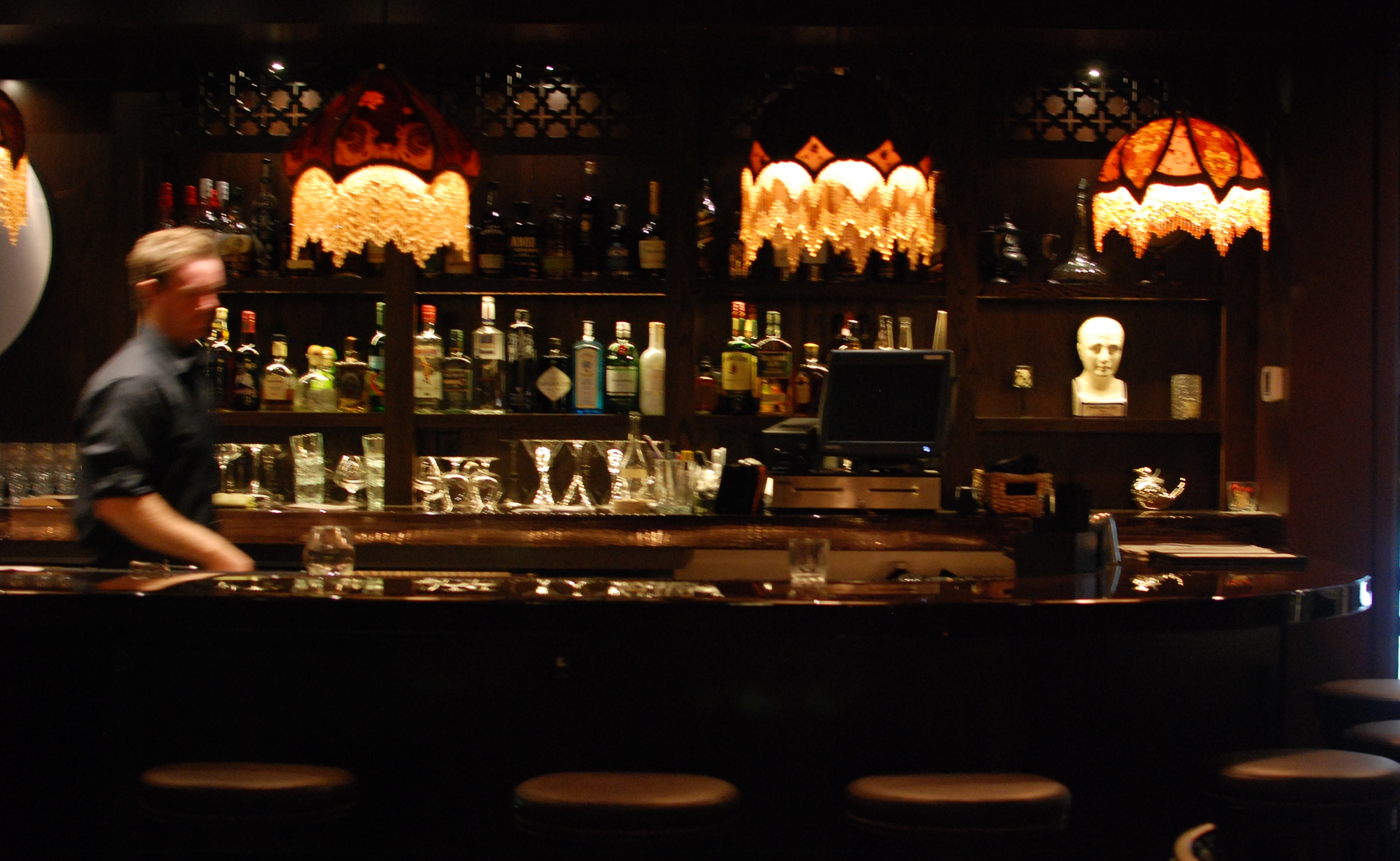 A darkened bar with wood top and back stocked with bottles. A blurred bartender walks past