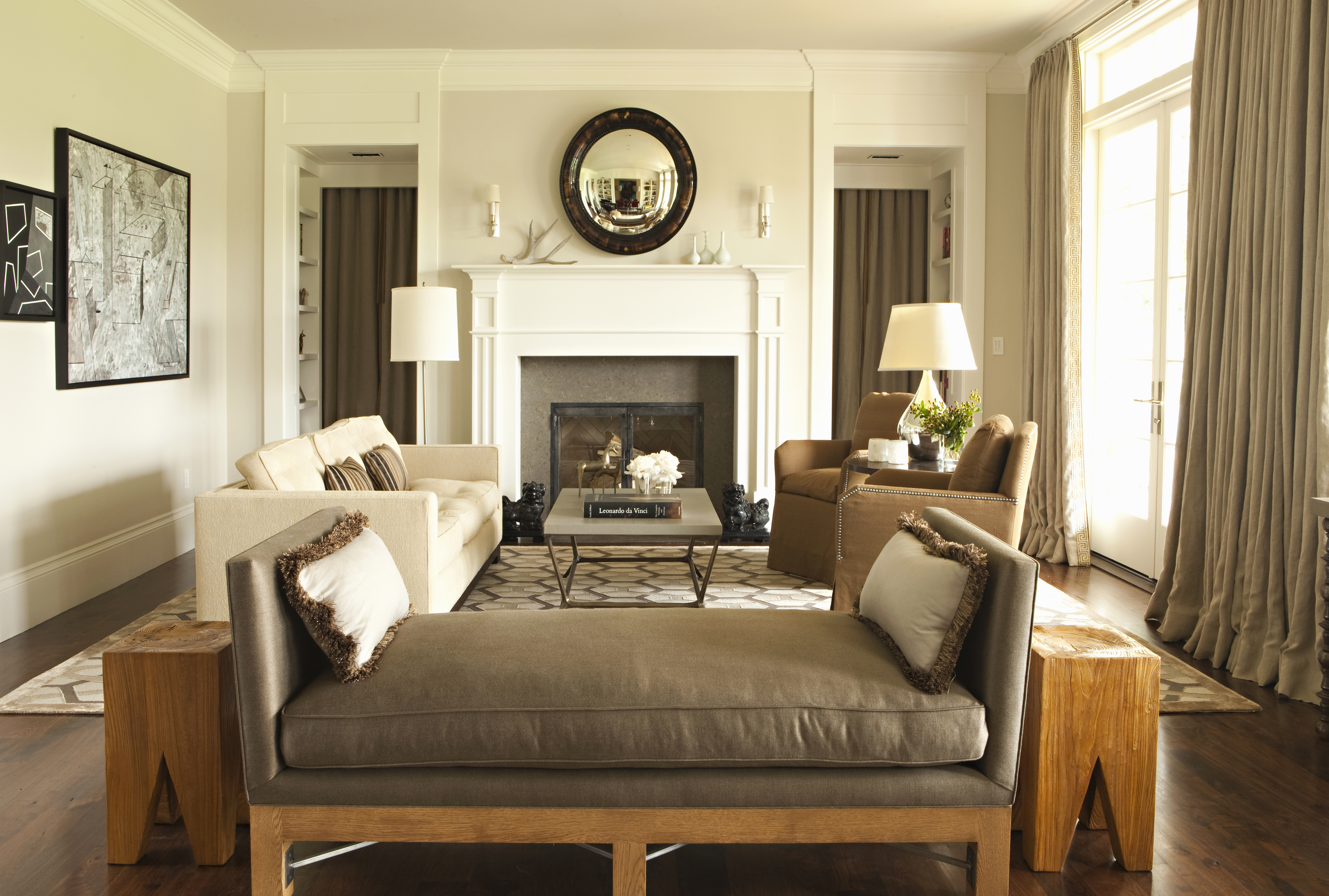 A living area with couches, arm chairs, a fireplace, works of art, a mirror, lamps, and an area rug. The walls are painted with a light grey beige color.