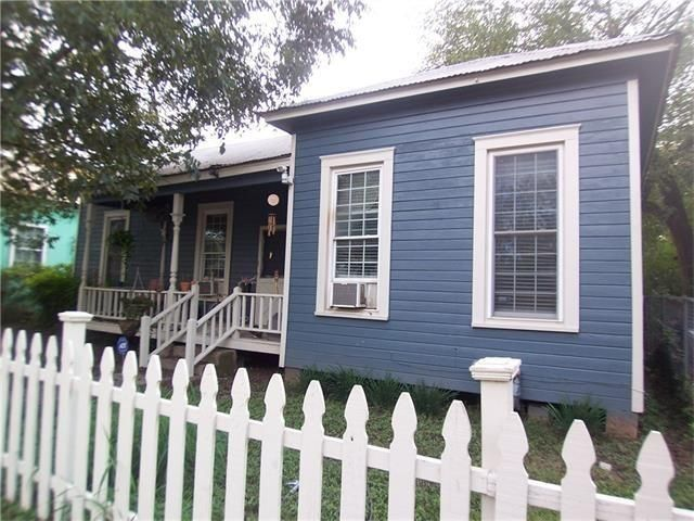 Small dark blue wood-frame house with white trim, large porch, and white picket fence
