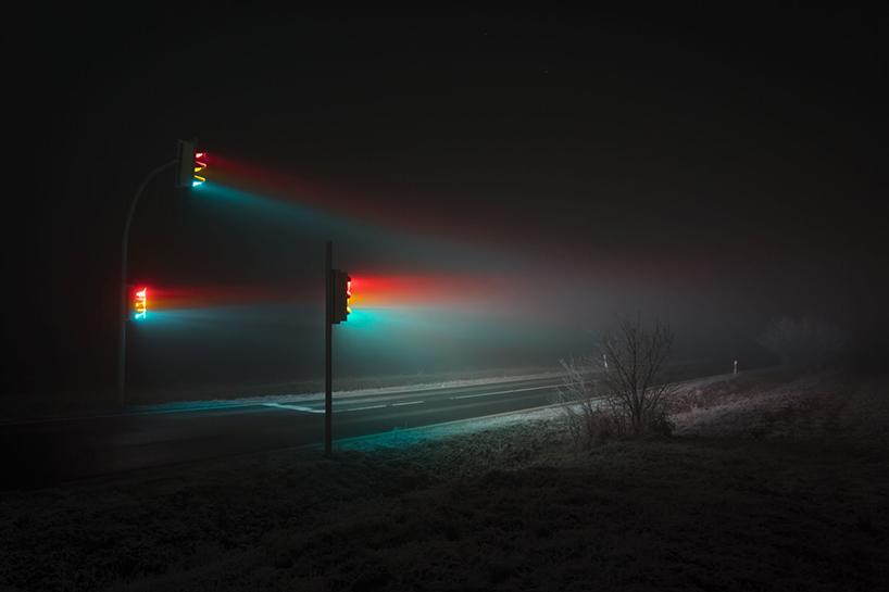 Night shot of three traffic lights emanating rainbow-like rays over an empty street.