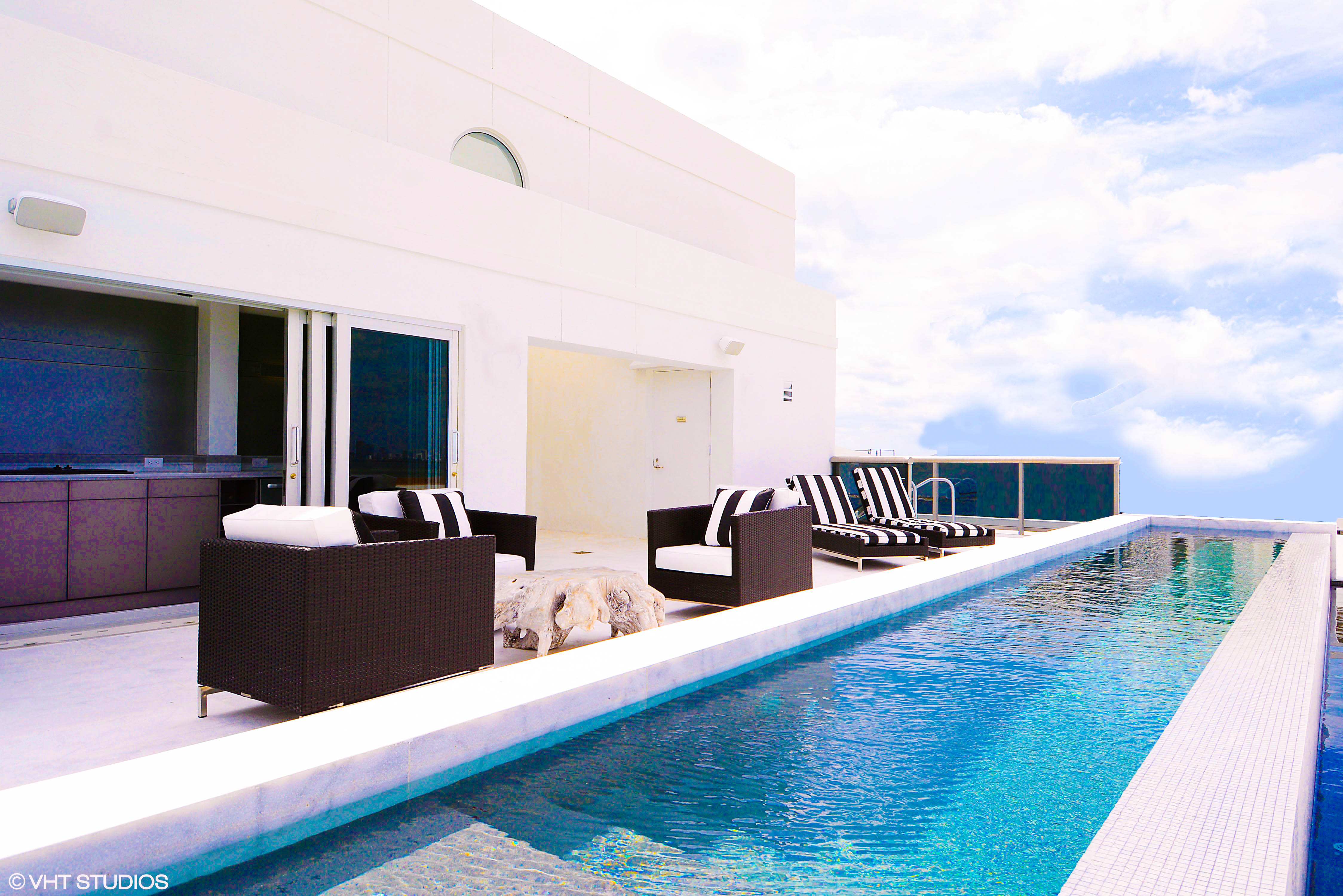 A rooftop penthouse with modern outdoor furniture on the terrace and a plunge pool