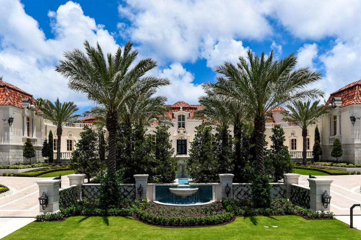 Front street view of a huge mansion in Palm Beach with palms, a dynamic driveway and a fountain out front.