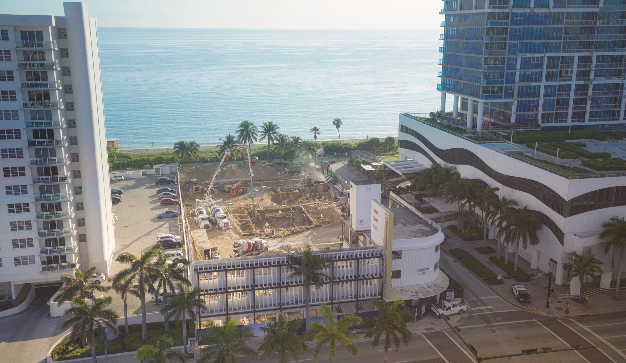 Aerial view of a concrete pour at L'Atelier Miami Beach with the ocean in the background