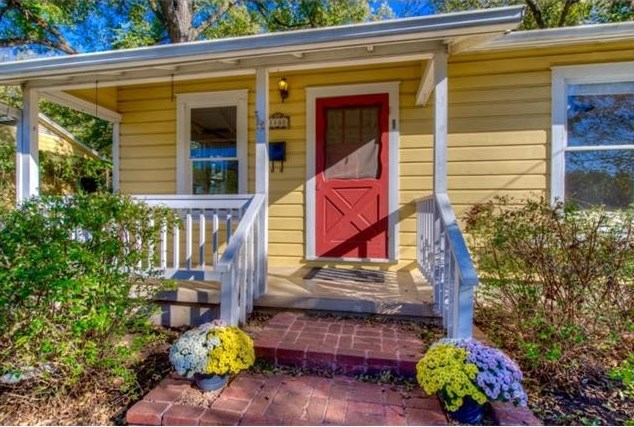 Small yellow wooden house with small porch, white railings and trim, red screen door