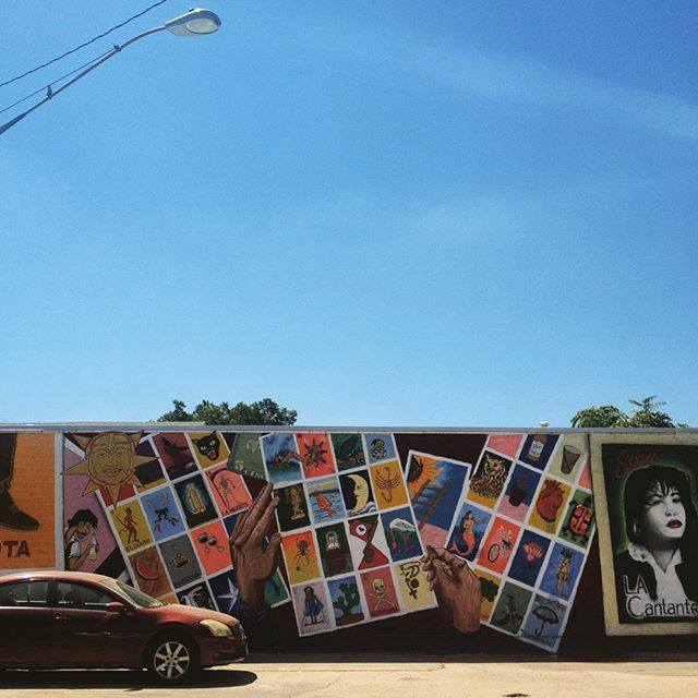 A building with Loteria game cards and Selena depicted on a mural with a car in front