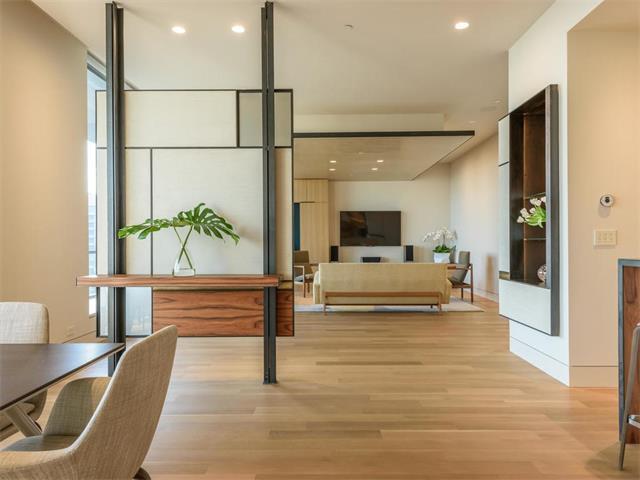 Midcentury-influenced modern open living room, beige, with low-slung furniture, blocked room divider, big window