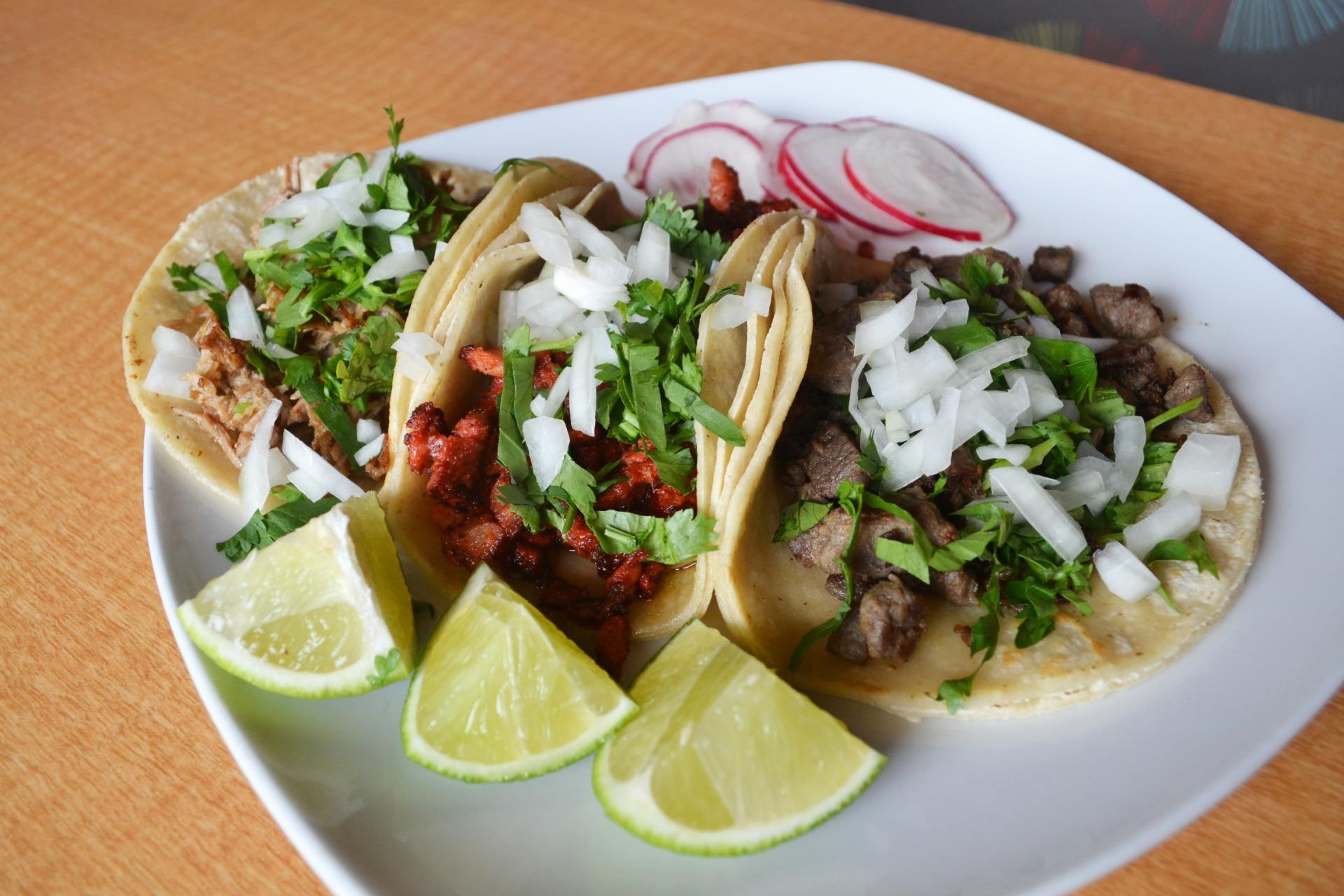 Carne asada, al pastor, and carnitas tacos from Los Ocampo on a white plate with three lime quarters, all three topped with chopped cilantro and onions.