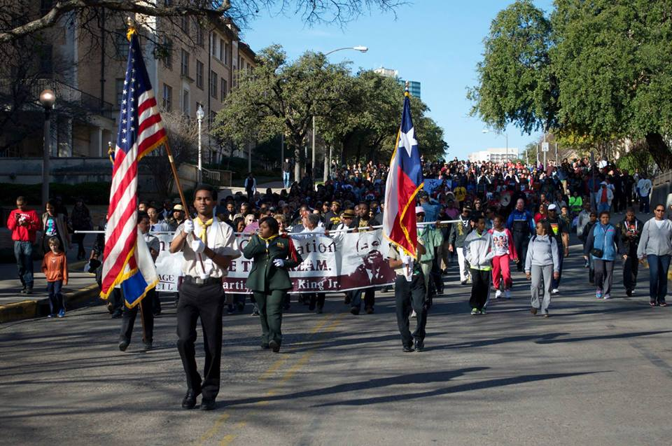 A large group of people marching down the street with U.S. and Texas flag-bearers in front and people holding a banner directly behind them