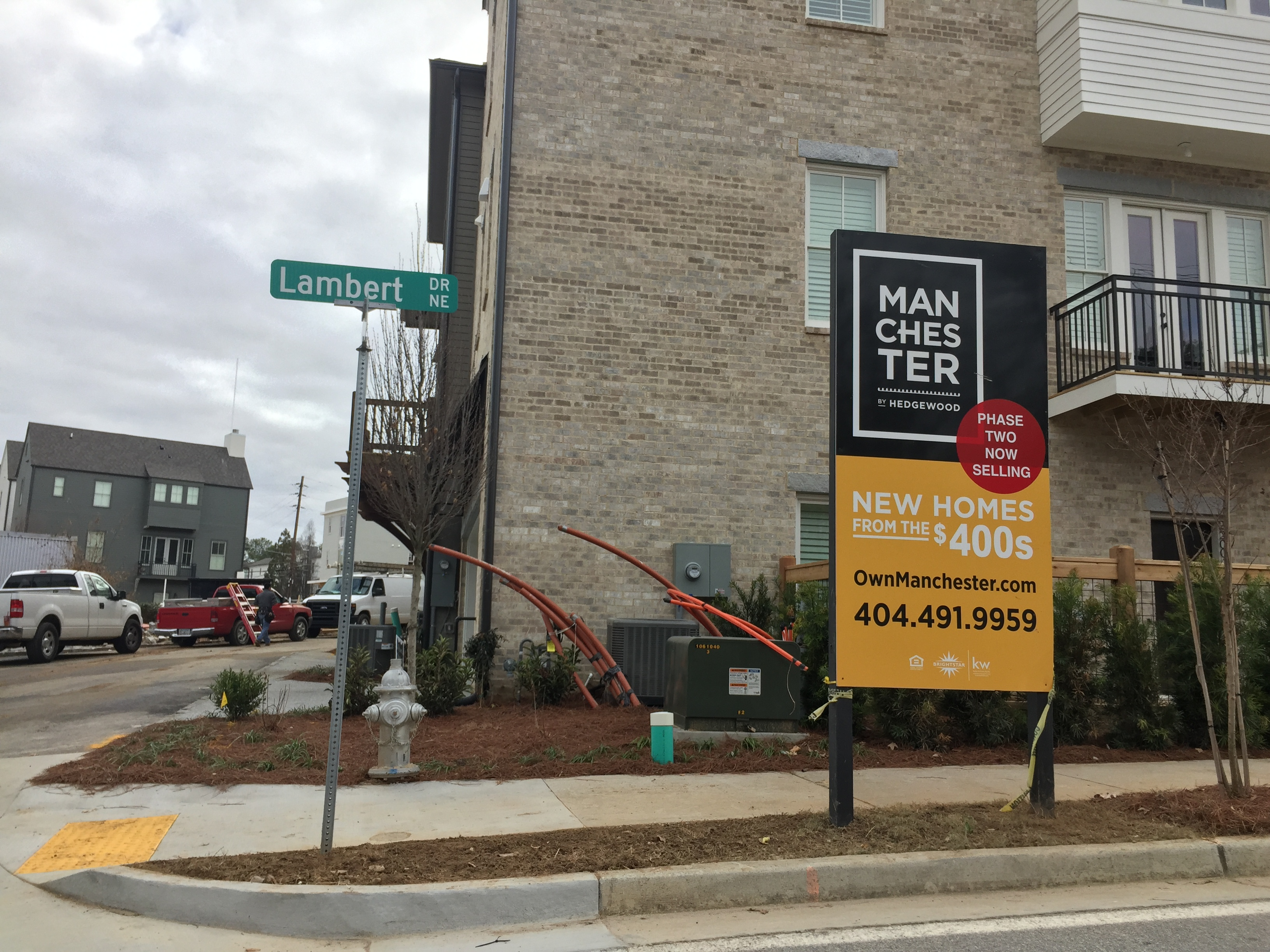 A sign for the development stands in front of new houses evoking old-town style.